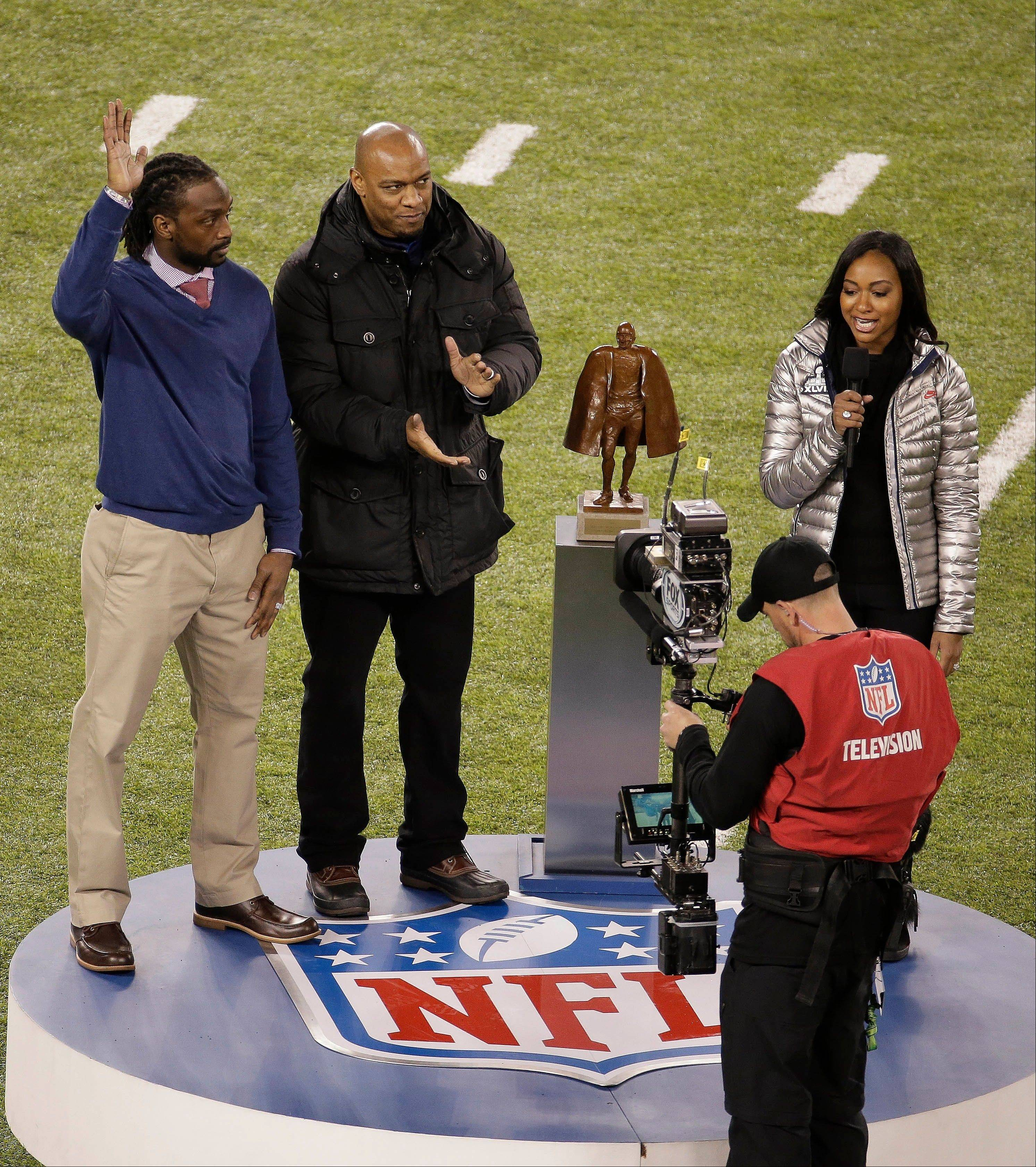Charles Tillman, of the Chicago Bears, left, reacts as he accepts the Walter Payton NFL Man of the Year award before the NFL Super Bowl XLVIII football game.