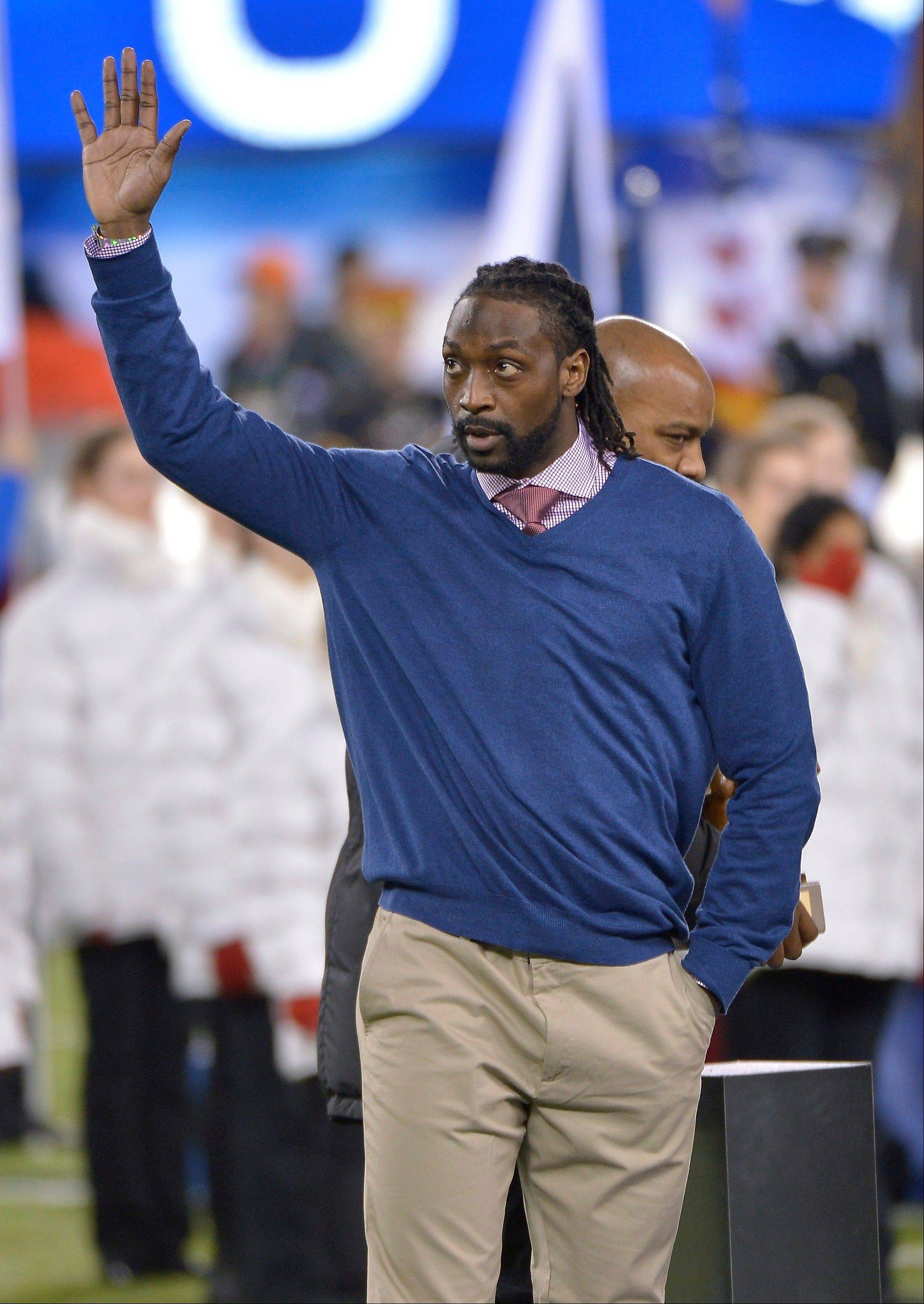 Chicago Bears' Charles Tillman waves after being introduced as the 2013 Walter Payton Man of the Year award winner before the NFL Super Bowl XLVIII football game.