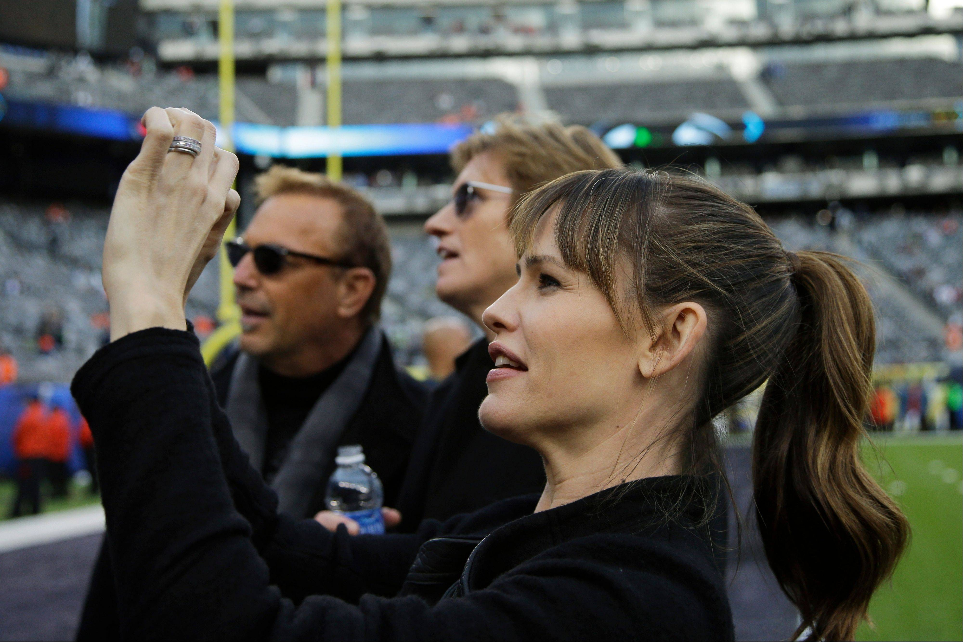 Actress Jennifer Garner takes a photo as actors Kevin Costner, left, and Denis Leary look on, at MetLife Stadium before the NFL Super Bowl XLVIII football game.