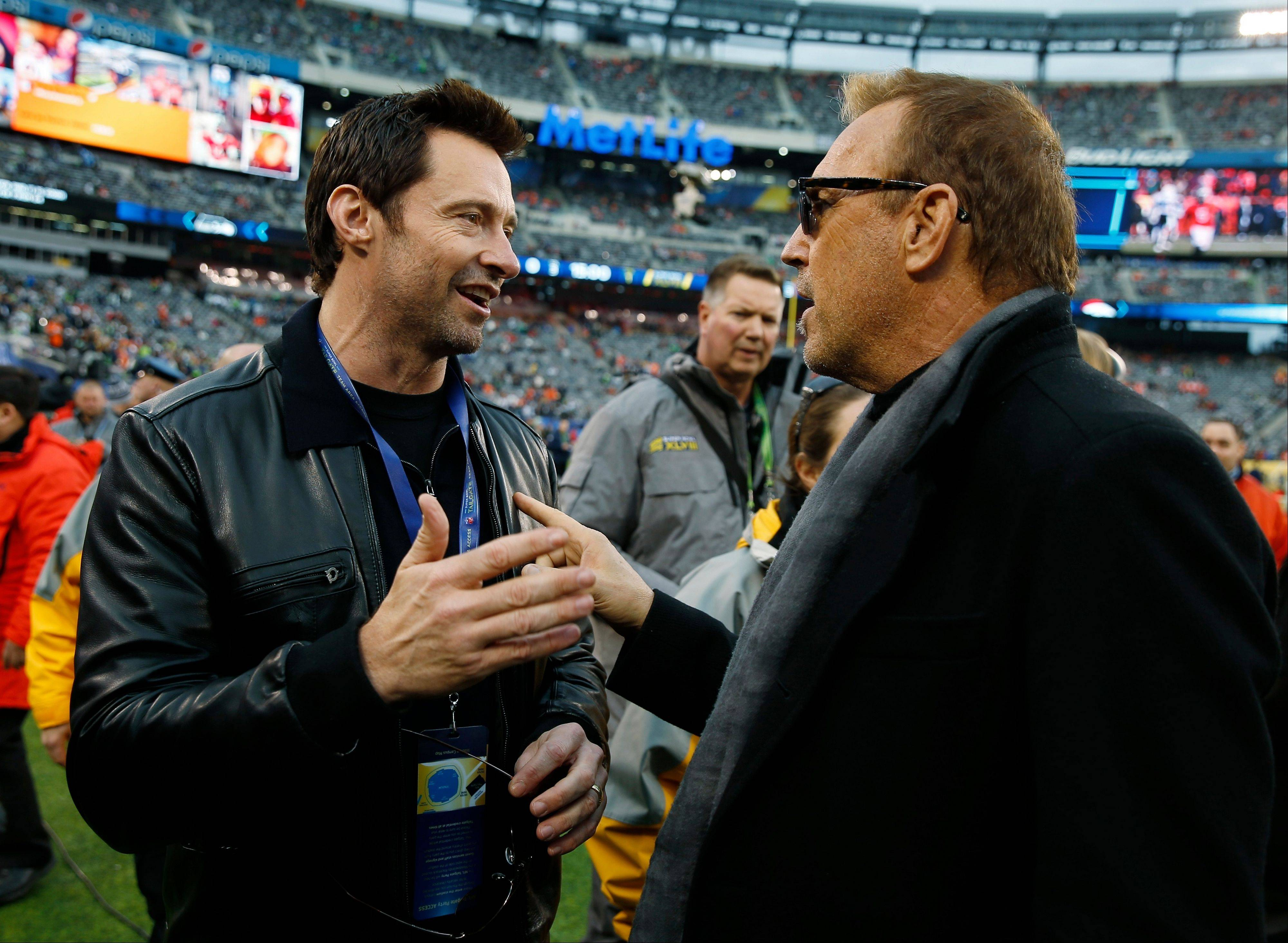 Actor Hugh Jackman, left, talks with fellow actor Kevin Costner, on the field before the NFL Super Bowl XLVIII football game.