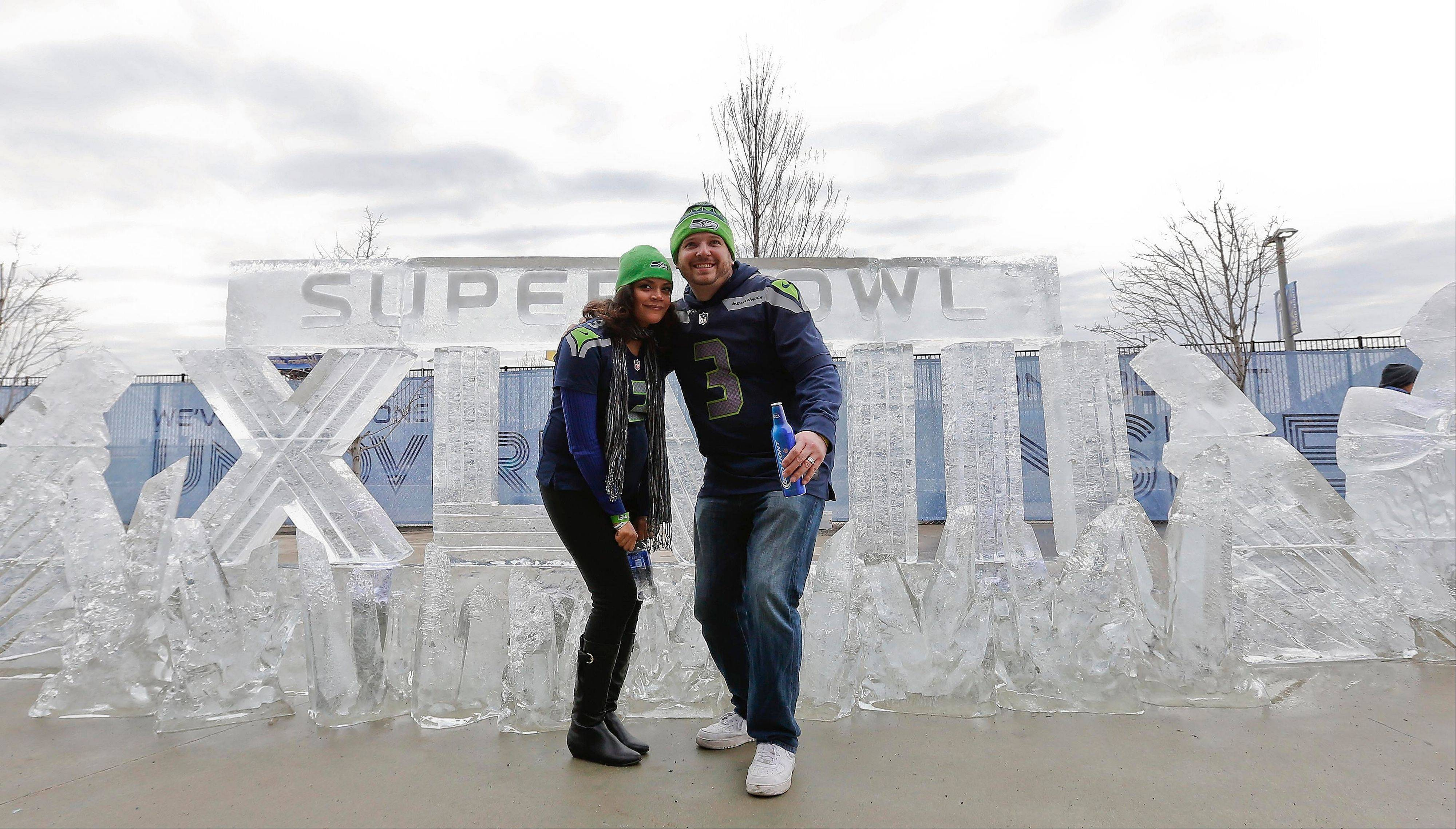 Seattle Seahawks fans Aaron Hulet, right, and Erica Hulet, pose for a picture in front of an ice sculpture before the NFL Super Bowl XLVIII football game.
