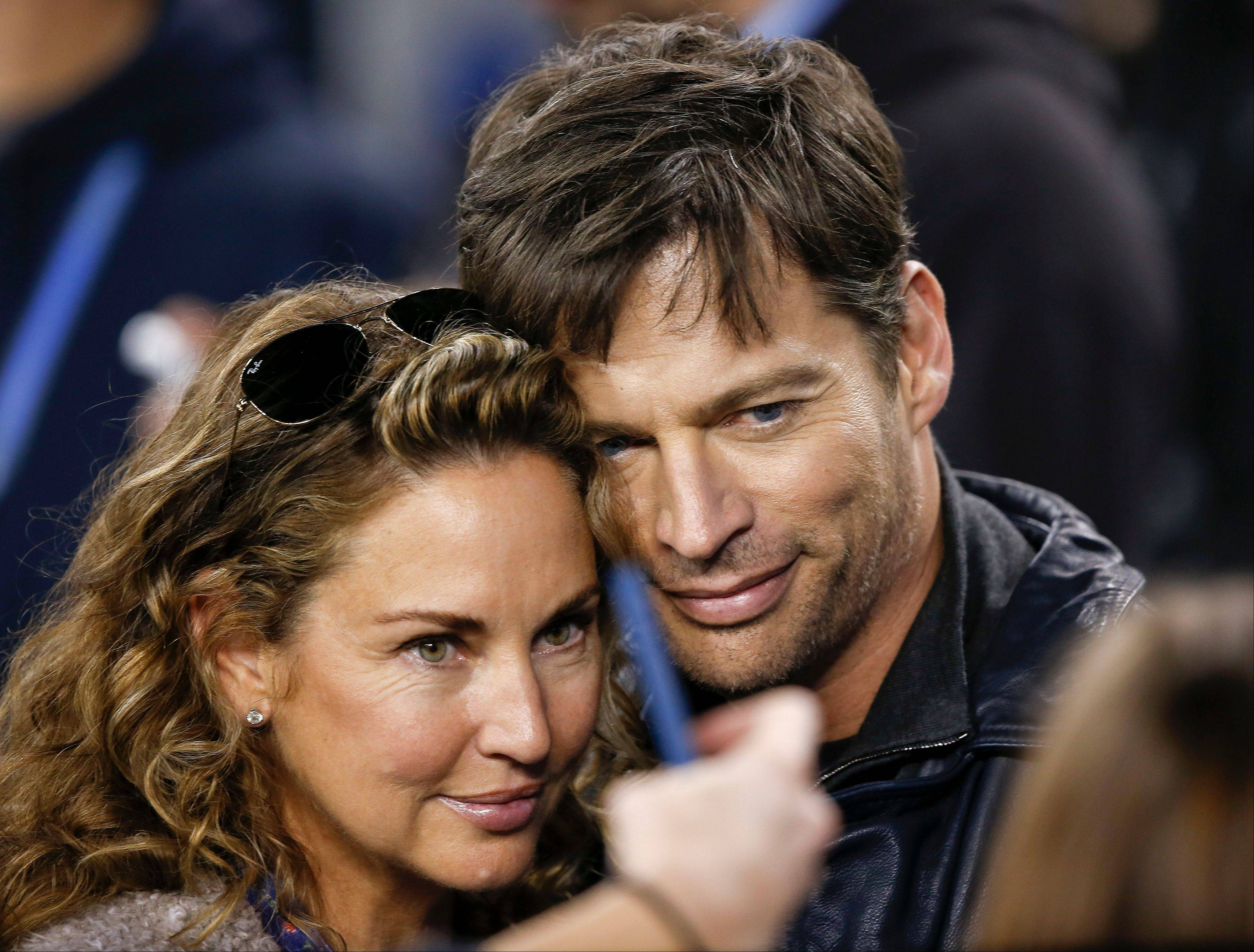 Harry Connick, Jr., right, poses for a picture with his wife, Jill Goodacre, before the NFL Super Bowl XLVIII football game.