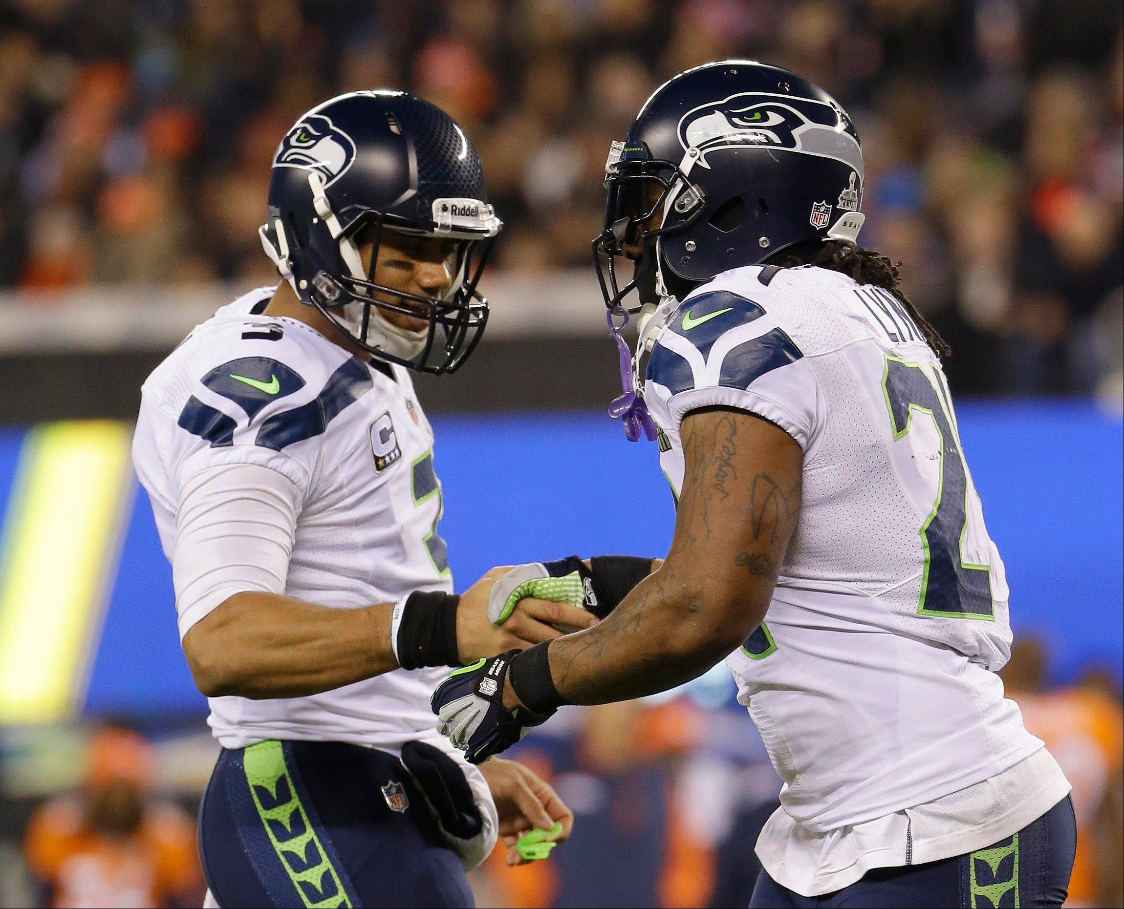 Seattle Seahawks' Russell Wilson, left, celebrates with teammate Marshawn Lynch during the first half of the NFL Super Bowl XLVIII football game against the Denver Broncos.