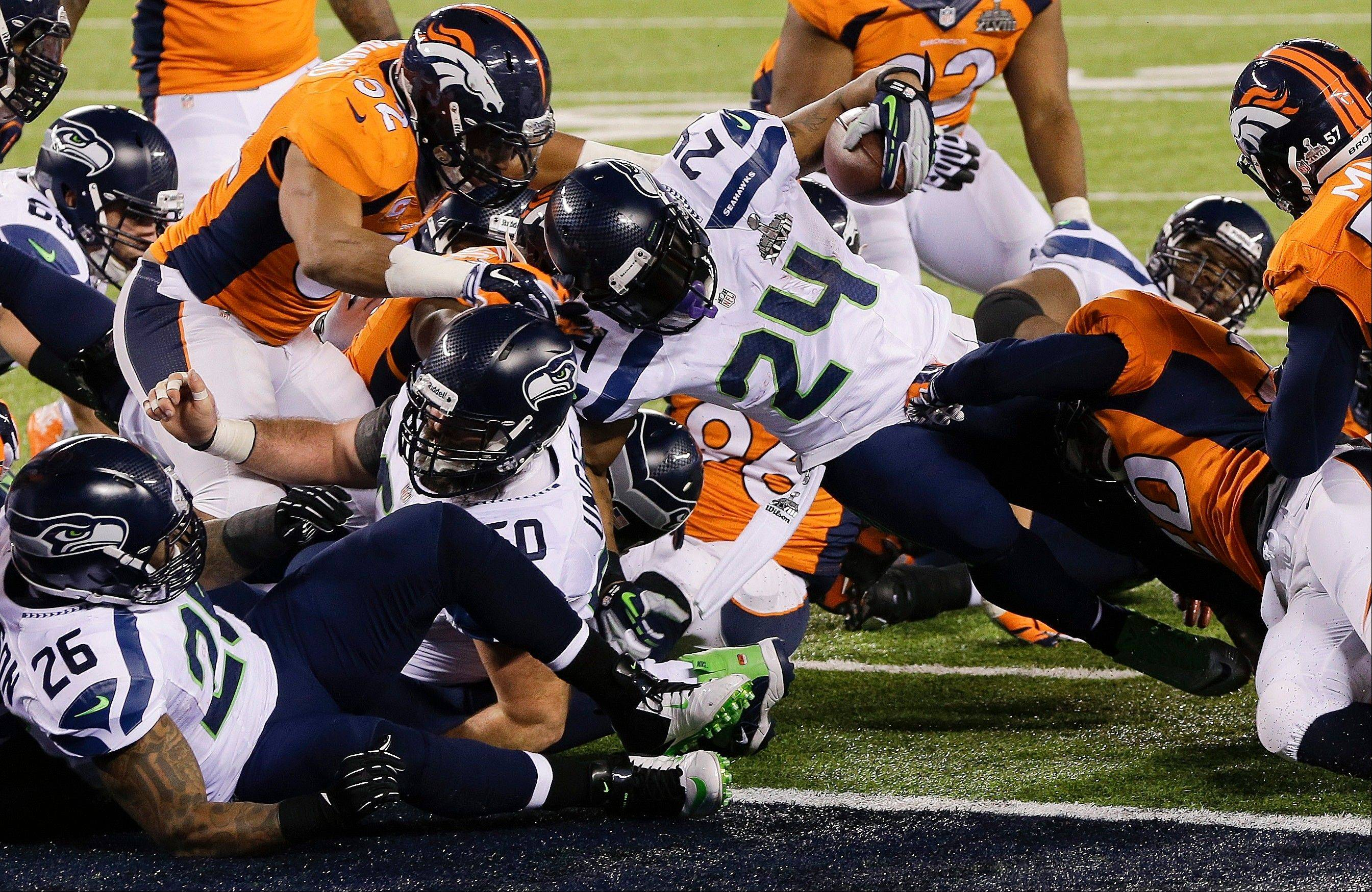 Seattle Seahawks running back Marshawn Lynch (24) pushes his way into the end zone for a touchdown run against the Denver Broncos during the first half.
