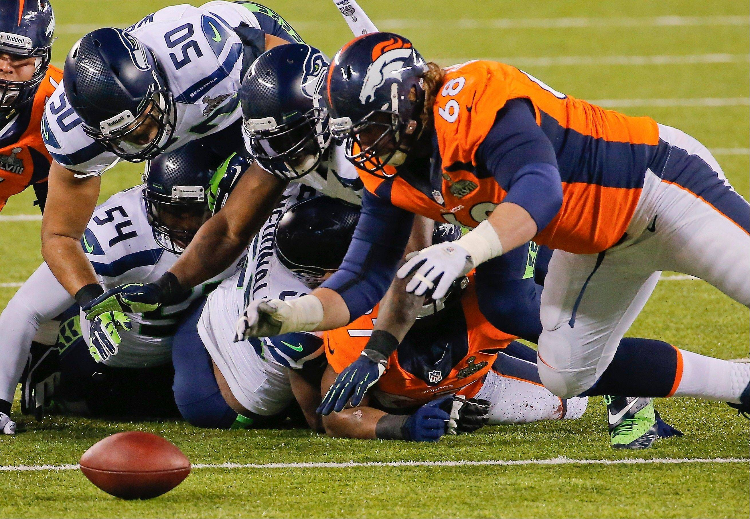 Seattle Seahawks' K.J. Wright (50), Chris Clemons (91) and Denver Broncos' Zane Beadles (68) dive after a fumble by the Broncos' Knowshon Moreno during the first half. Beadles recovered the ball on the play.
