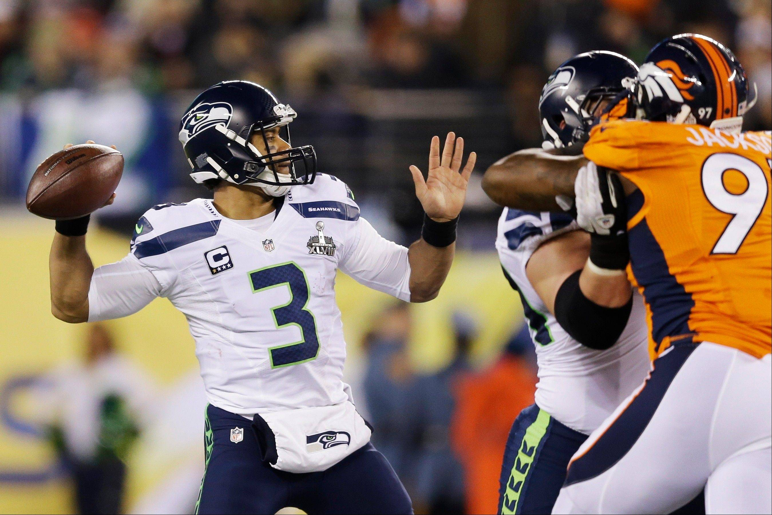 Seattle Seahawks' Russell Wilson (3) throws against the Denver Broncos during the first half.