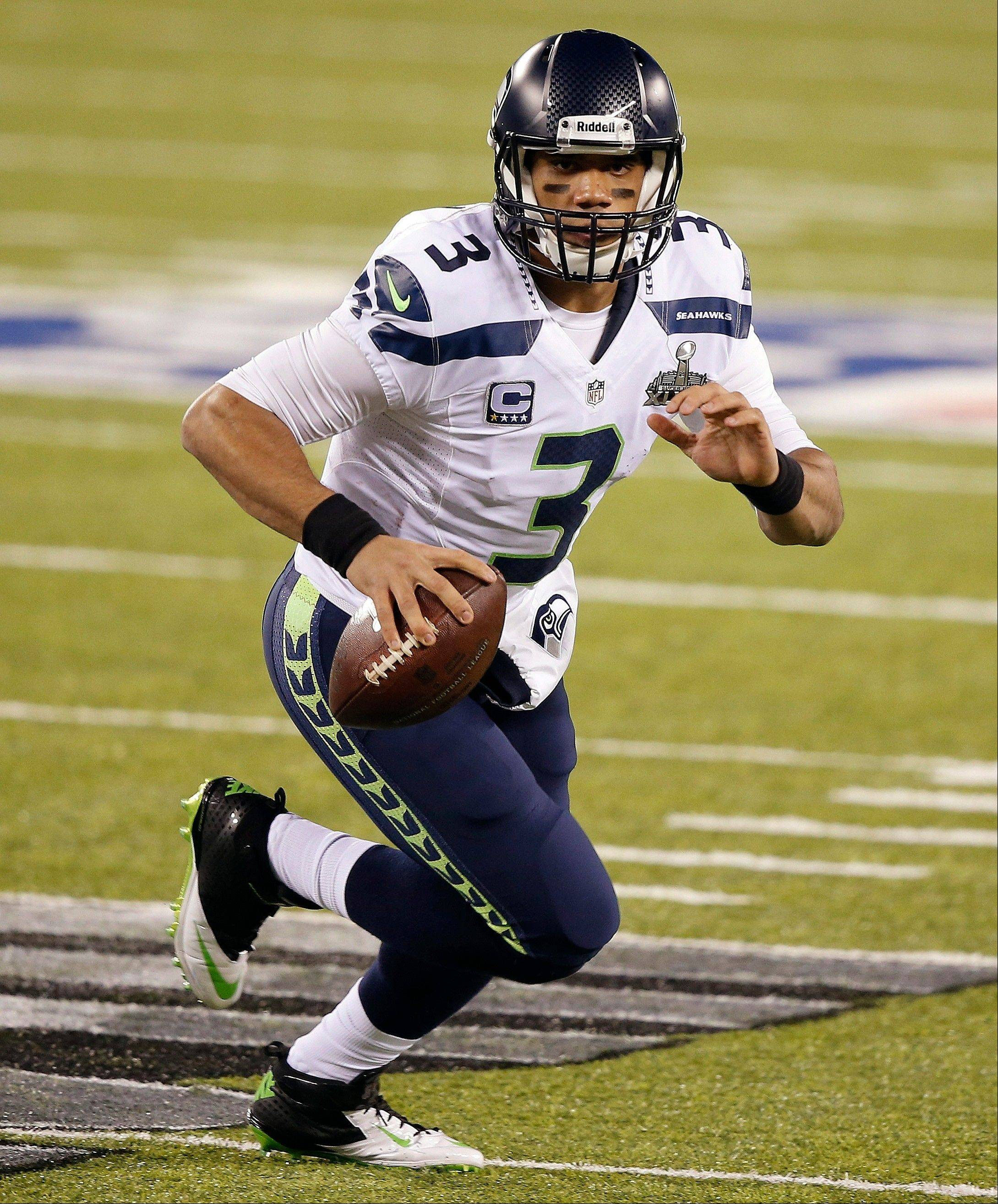 Seattle Seahawks quarterback Russell Wilson scrambles out of the pocket during the first half.
