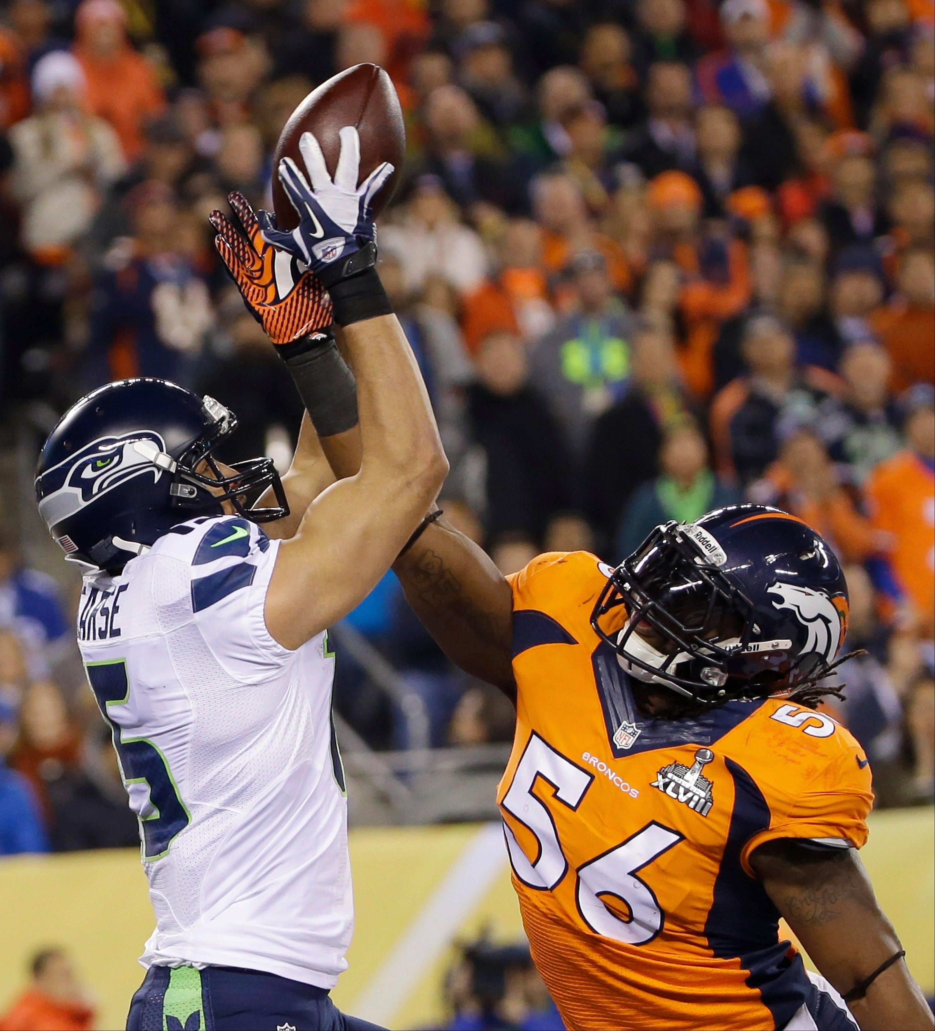Denver Broncos' Nate Irving (56) breaks up a pass intended for Seattle Seahawks' Jermaine Kearse, left, during the first half.