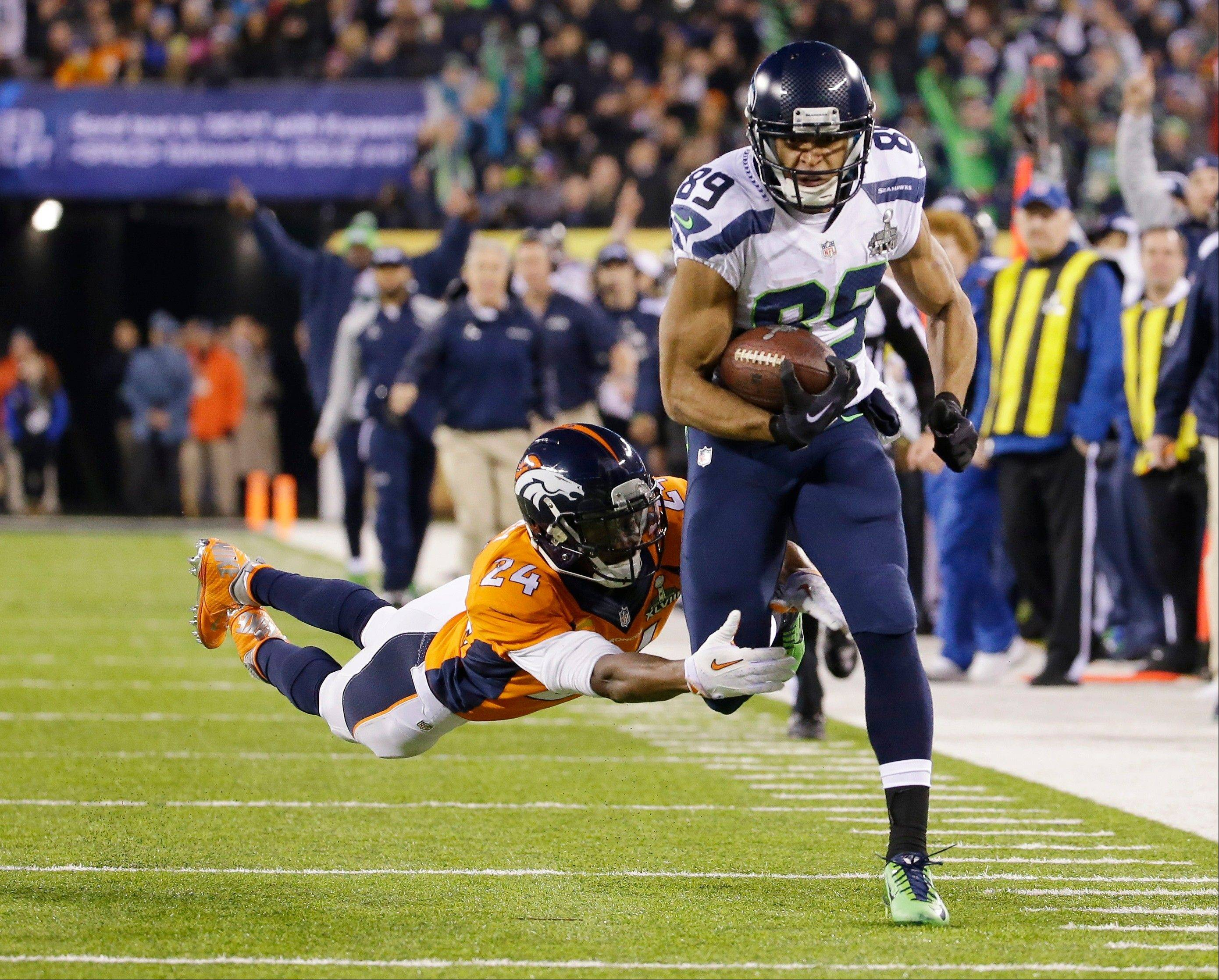 Seattle Seahawks' Doug Baldwin (89) runs from Denver Broncos' Champ Bailey (24) after making a reception during the first half.
