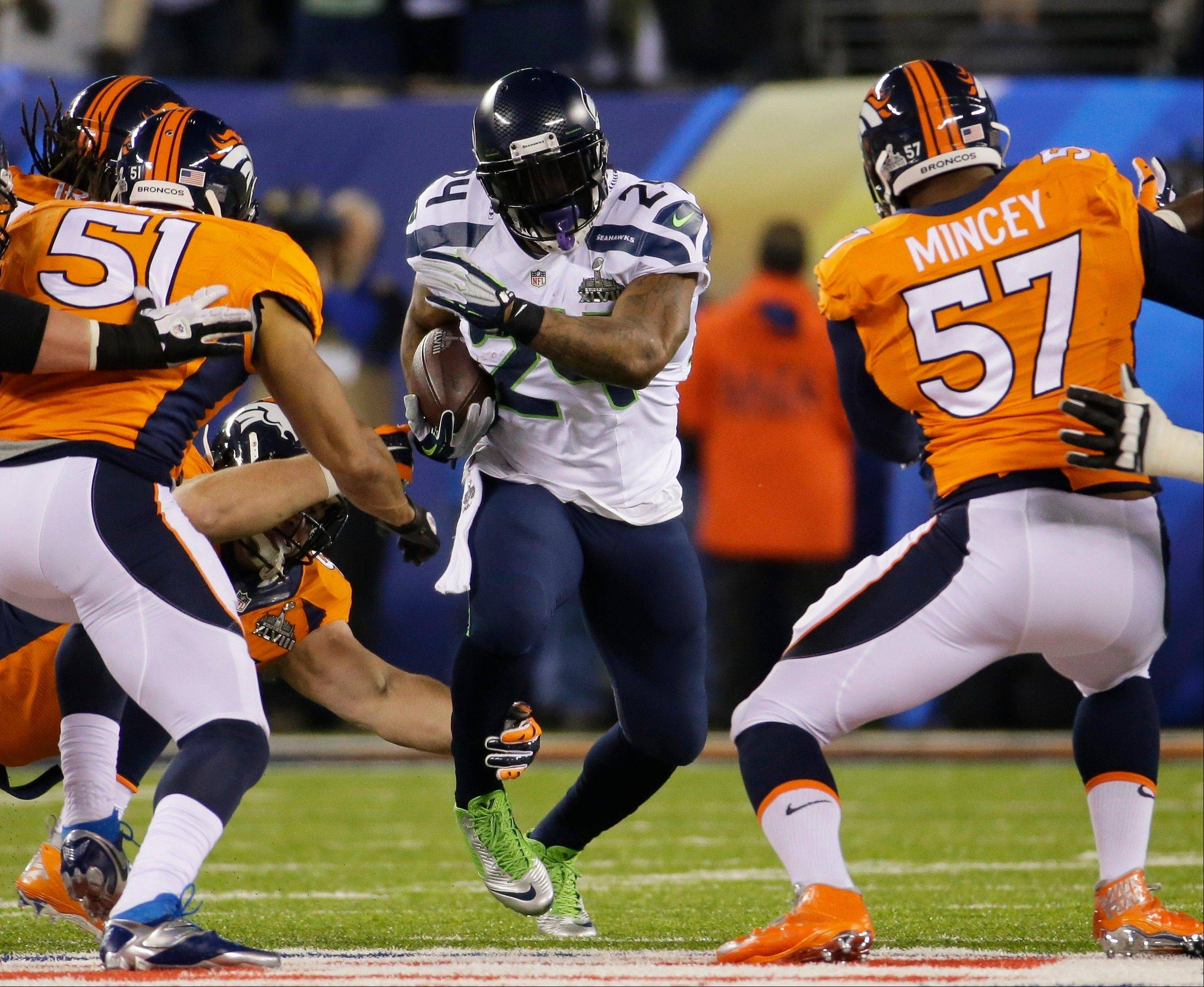Seattle Seahawks' Marshawn Lynch (24) runs between Denver Broncos' Paris Lenon, left, and Jeremy Mincey, right, during the first half.