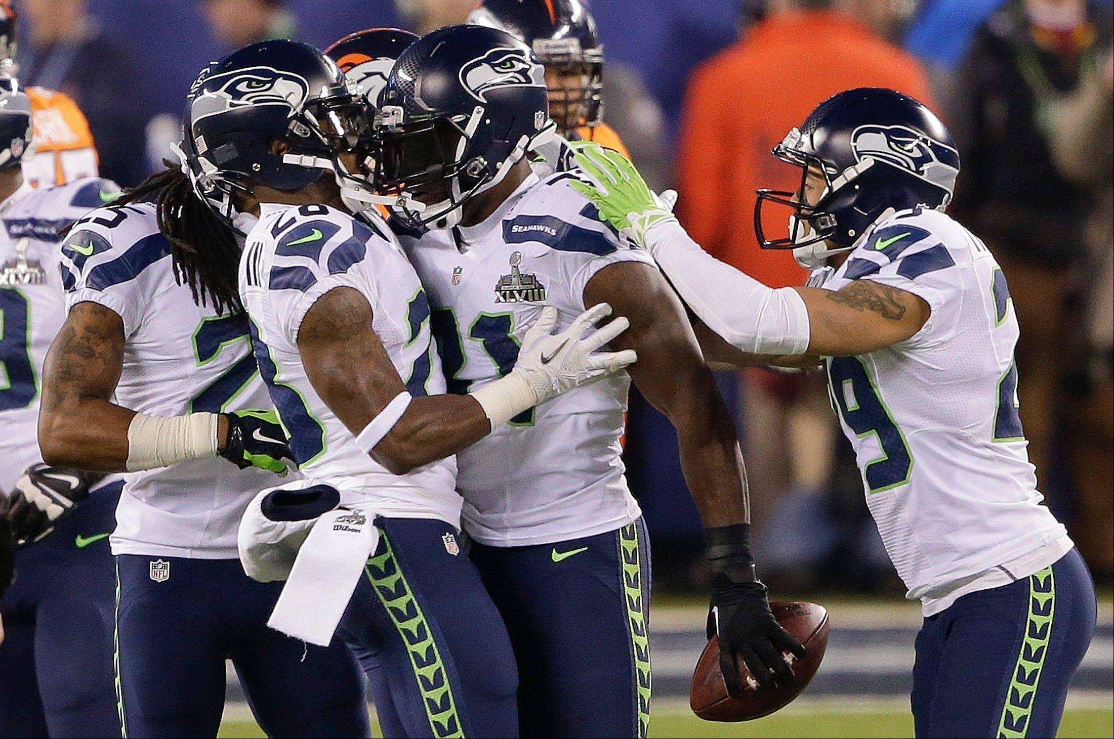 Seattle Seahawks strong safety Kam Chancellor (31) celebrates with teammates after intercepting a pass during the first half.
