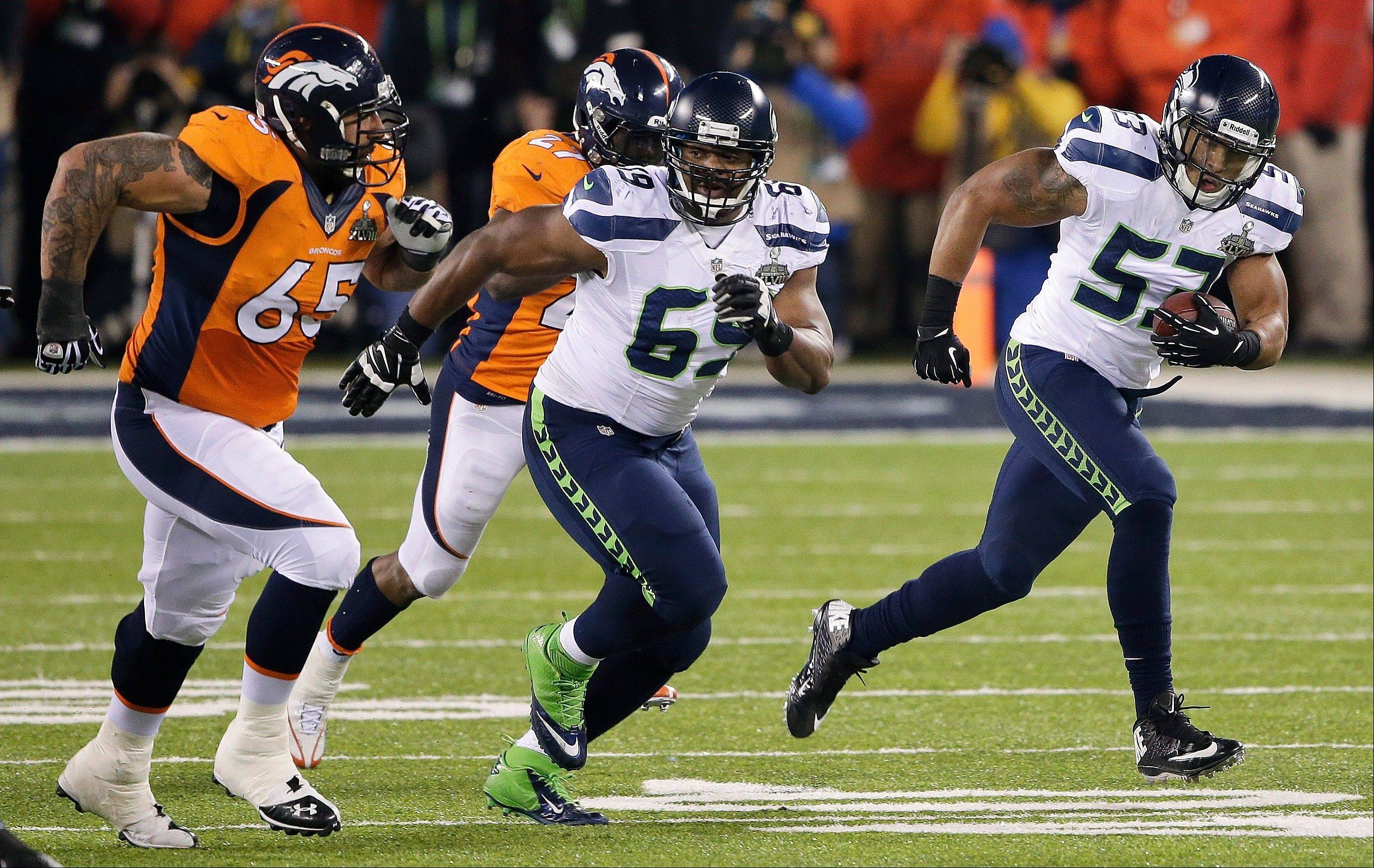 Seattle Seahawks outside linebacker Malcolm Smith (53) breaks down the field to return an interception for a touchdown against the Denver Broncos during the first half.
