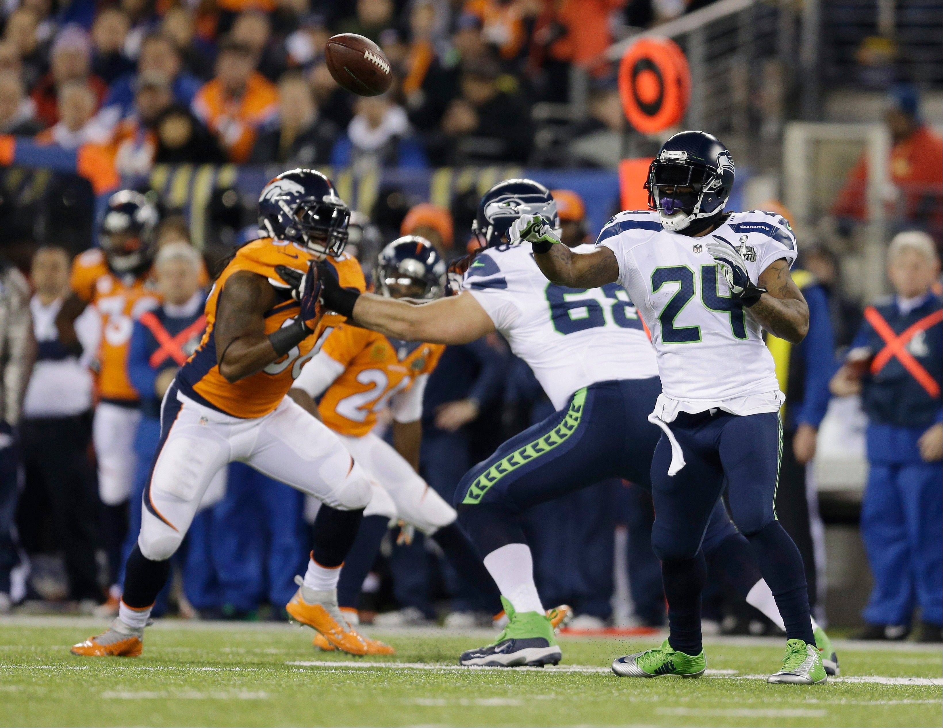 Seattle Seahawks' Marshawn Lynch (24) throws a pass to teammate Russell Wilson during the first half.
