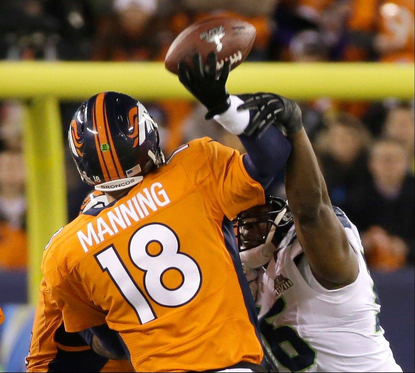 Denver Broncos' Peyton Manning is hit by Seattle Seahawks' Cliff Avril as he throws an interception during the first half.
