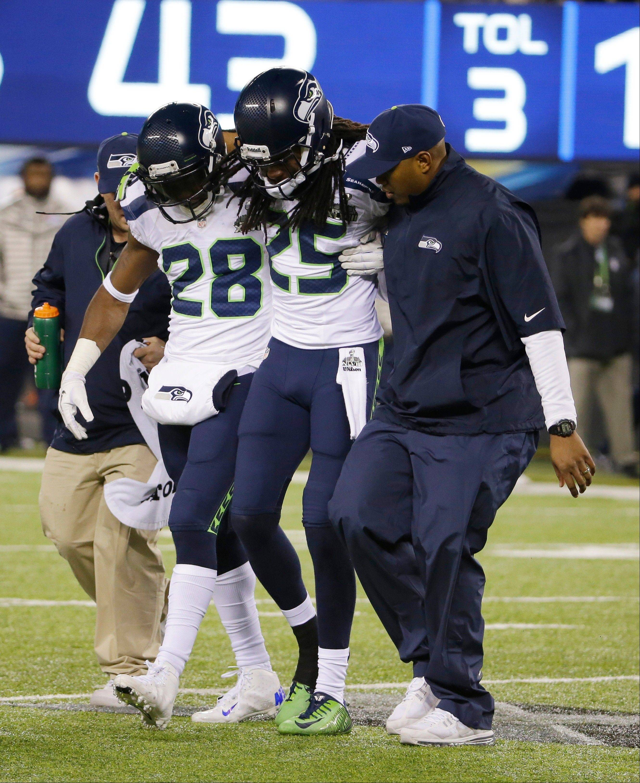 Seattle Seahawks' Richard Sherman (25) is helped off the field after getting injured during the second half.