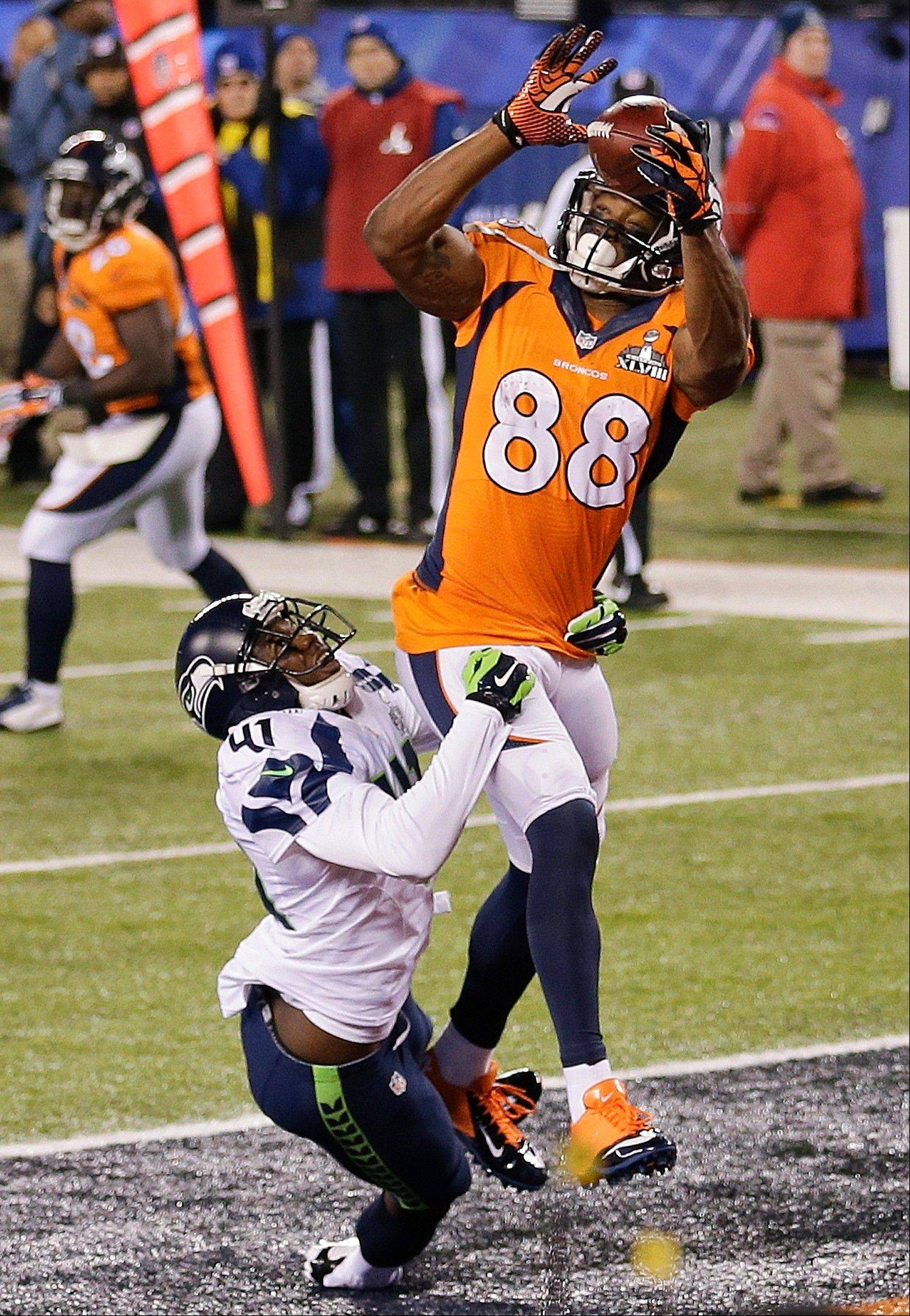Denver Broncos wide receiver Demaryius Thomas (88) is hit by Seattle Seahawks cornerback Byron Maxwell (41) as he makes a touchdown catch during the second half.