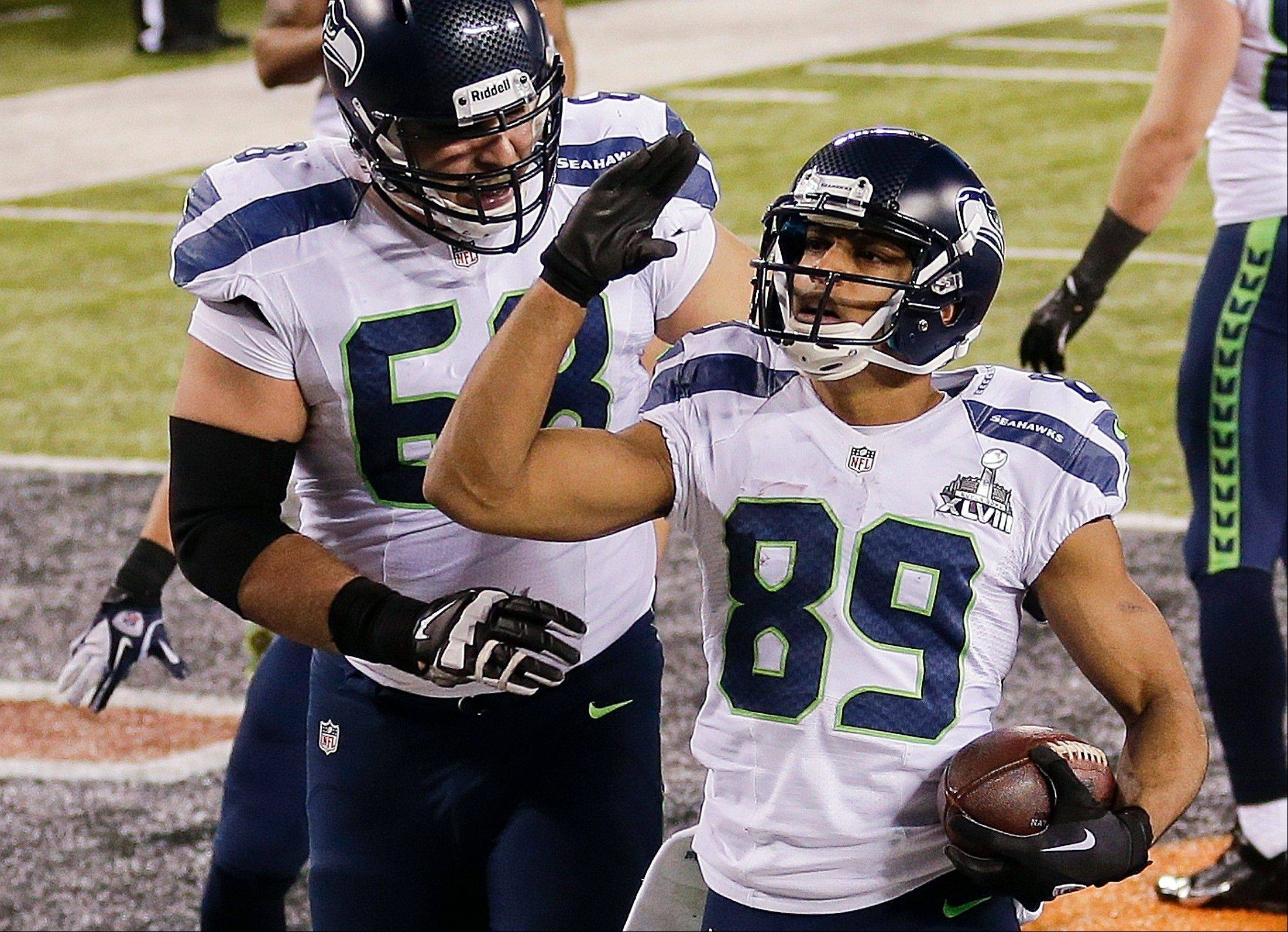 Seattle Seahawks wide receiver Doug Baldwin (89) celebrates with tackle Breno Giacomini (68) after scoring a touchdown against the Denver Broncos during the second half.