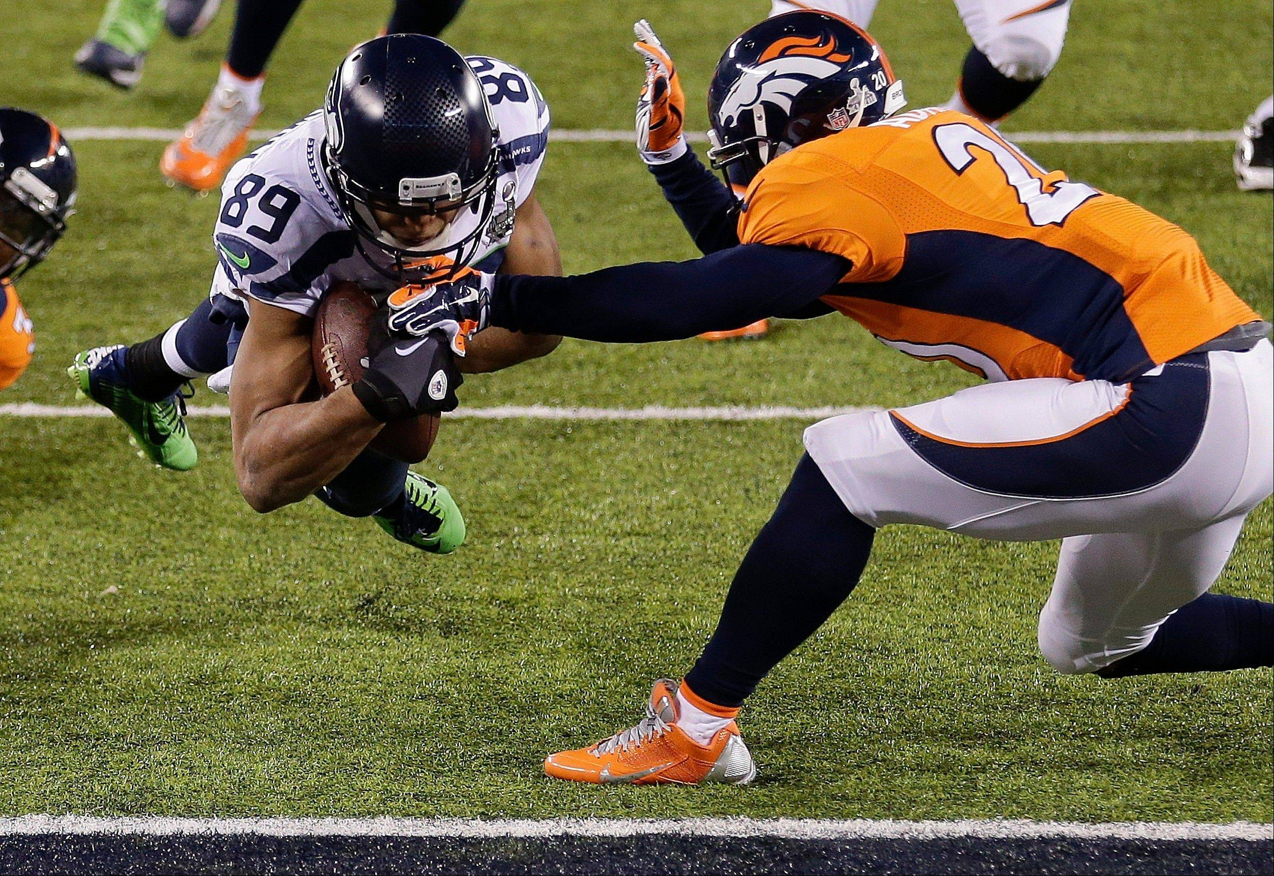 Seattle Seahawks wide receiver Doug Baldwin (89) dives into the end zone for a touchdown against Denver Broncos free safety Mike Adams (20) during the second half.