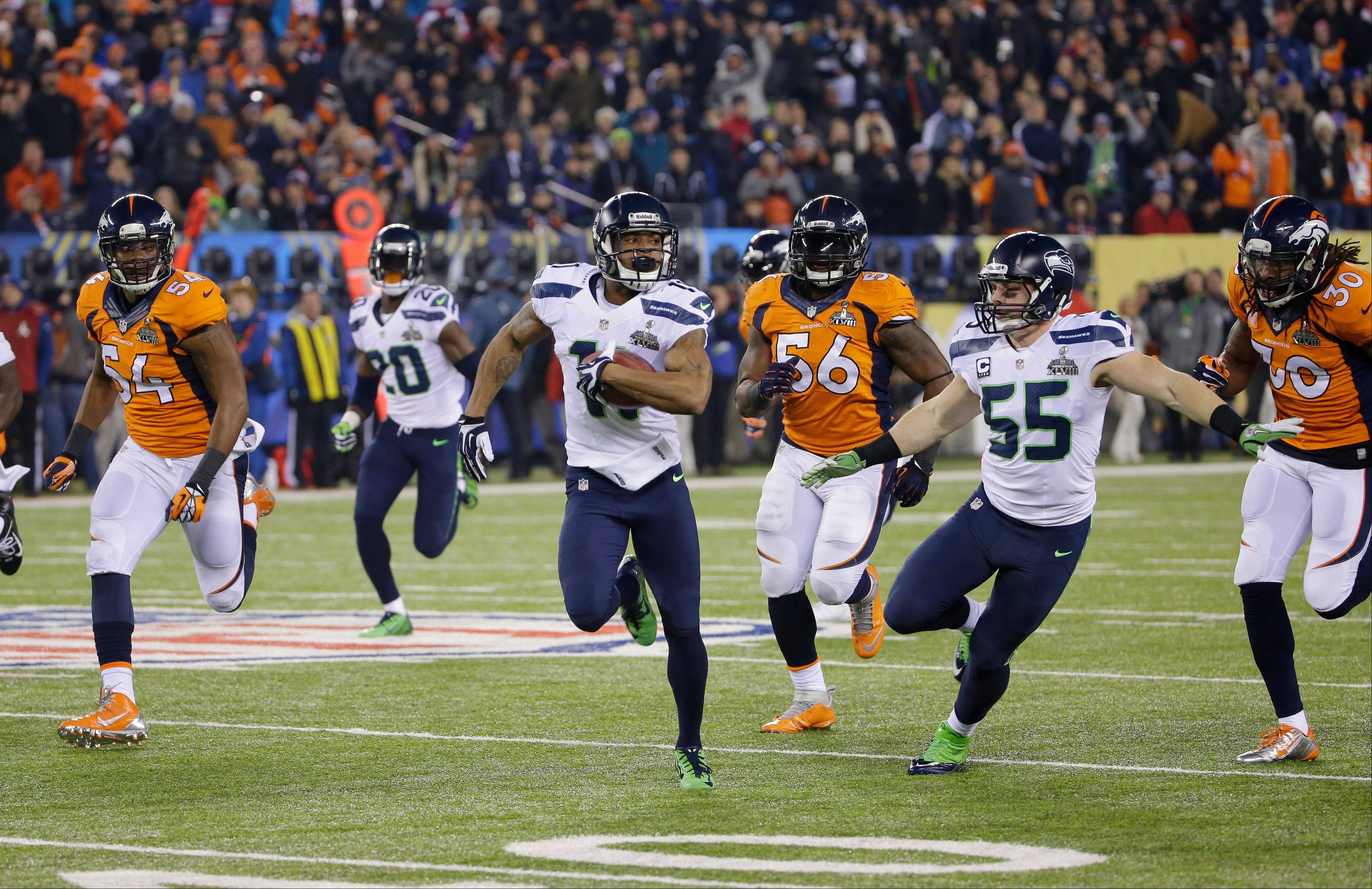 Seattle Seahawks' Percy Harvin, center, returns a kickoff 87-yards for a touchdown during the second half.