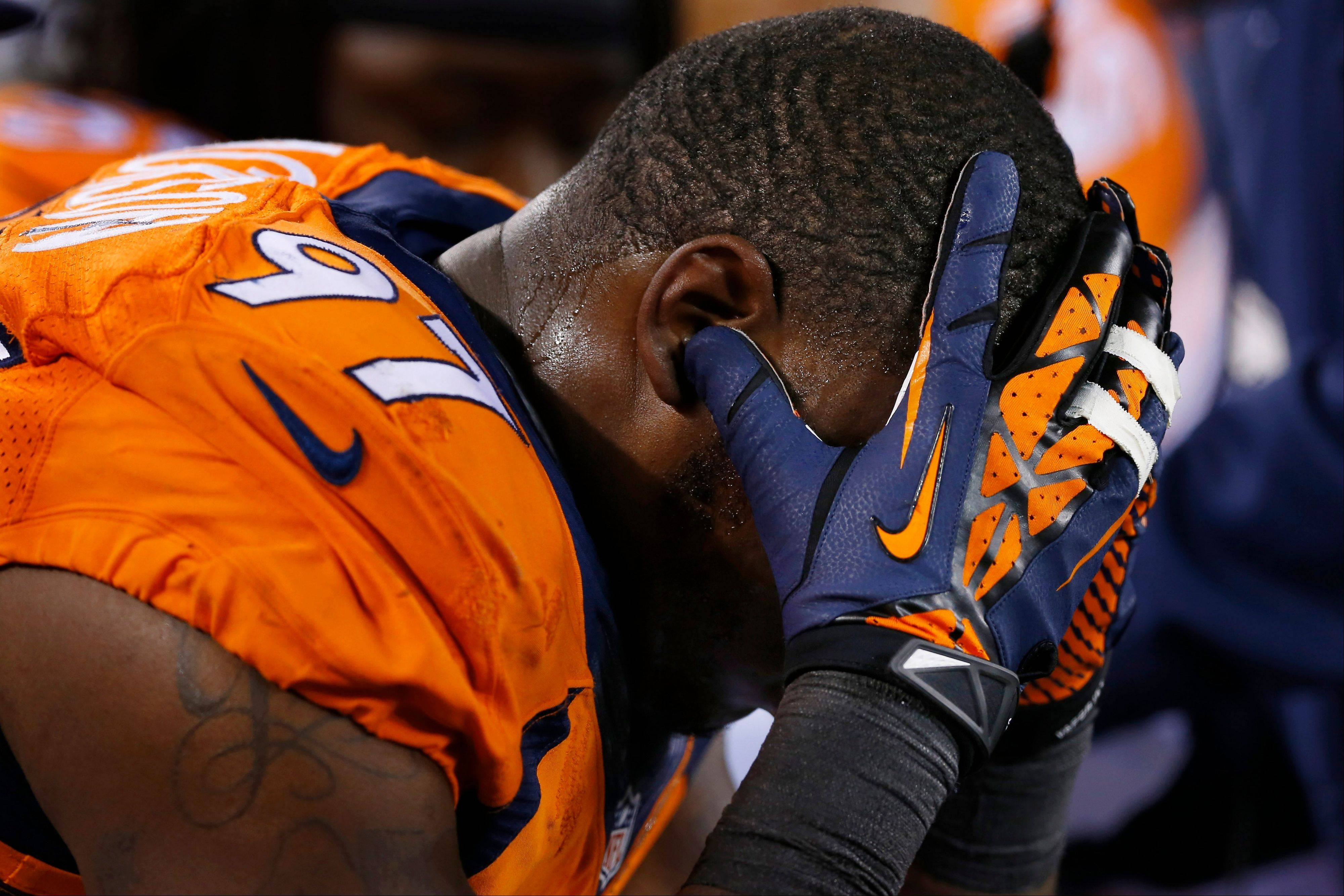Denver Broncos' Malik Jackson cradles his head on the sidelines during the second half.