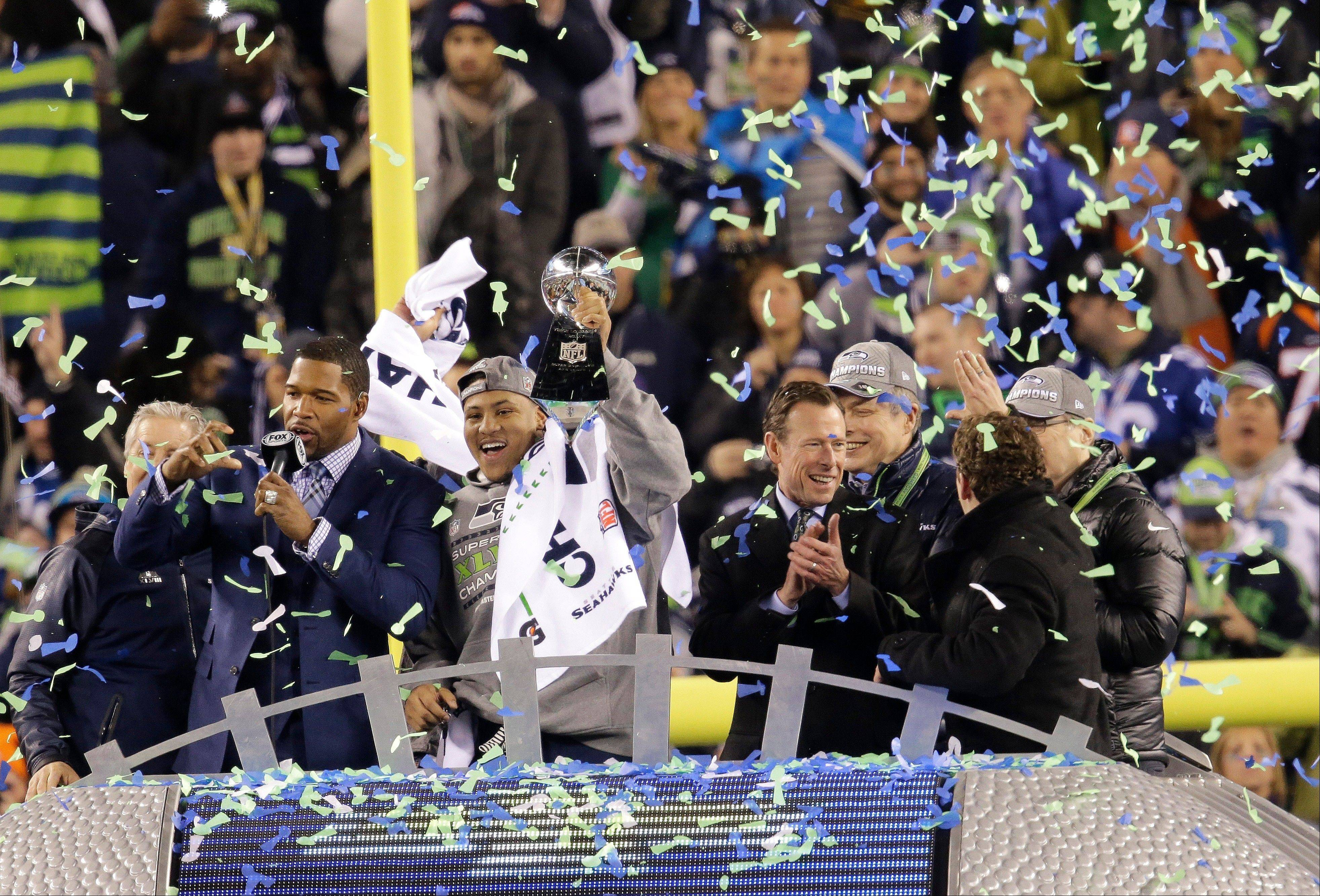 Seattle Seahawks' Malcolm Smith, center, celebrates with president Peter McLoughlin, center right, after the NFL Super Bowl XLVIII football game against the Denver Broncos.