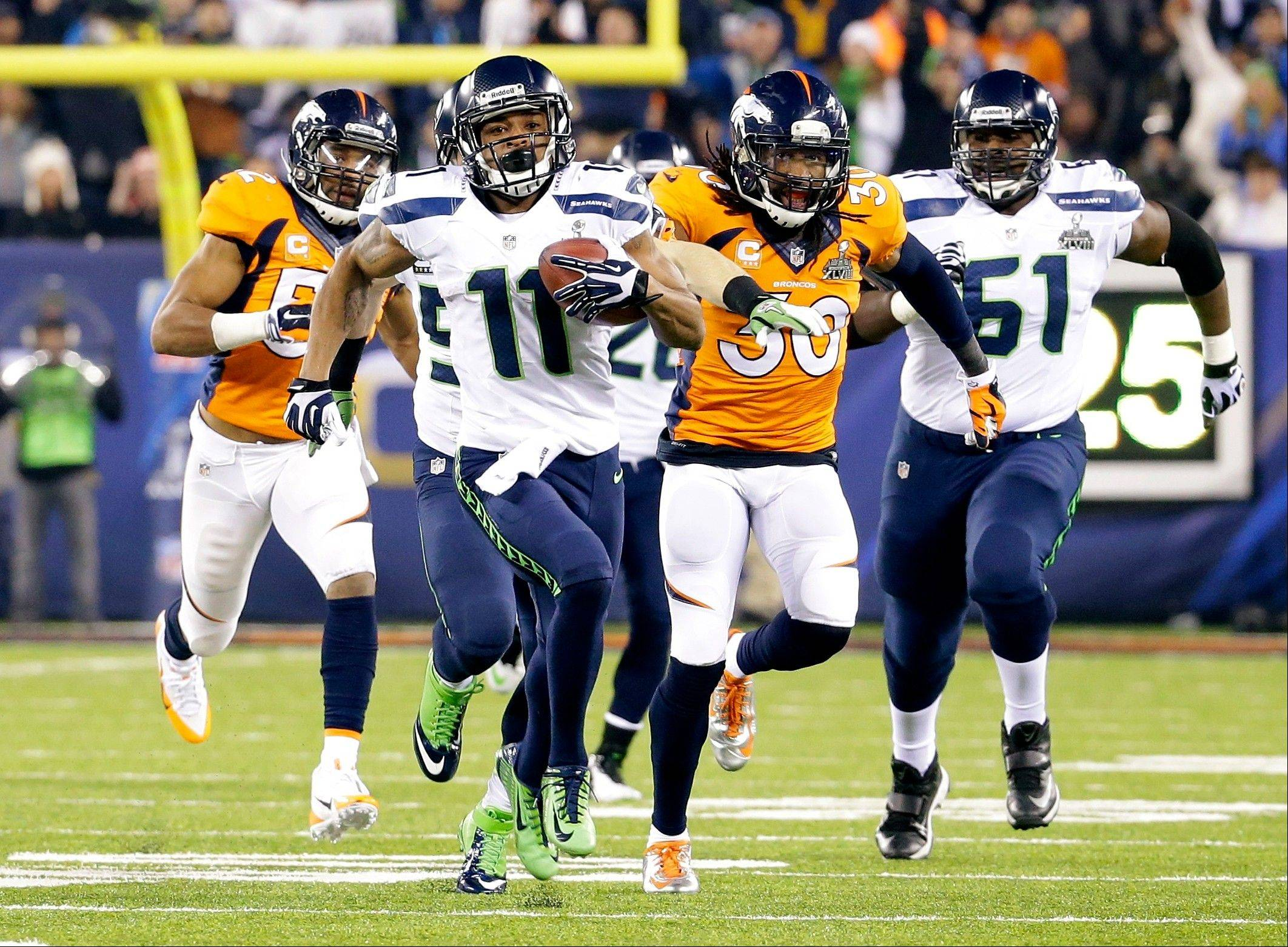 Seattle Seahawks' Percy Harvin (11) runs from Denver Broncos' David Bruton (30) while returning a kickoff 87-yards for a touchdown during the second half.