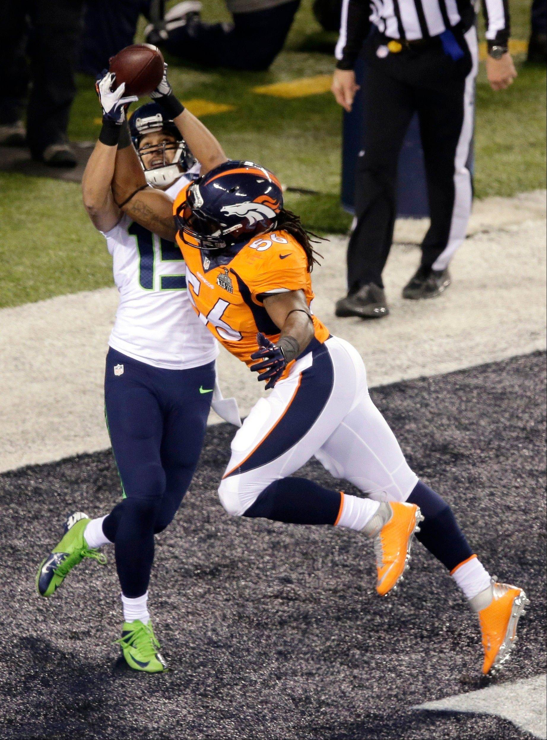 Denver Broncos' Nate Irving (56) breaks up a pass to Seattle Seahawks' Jermaine Kearse (15) during the first half.