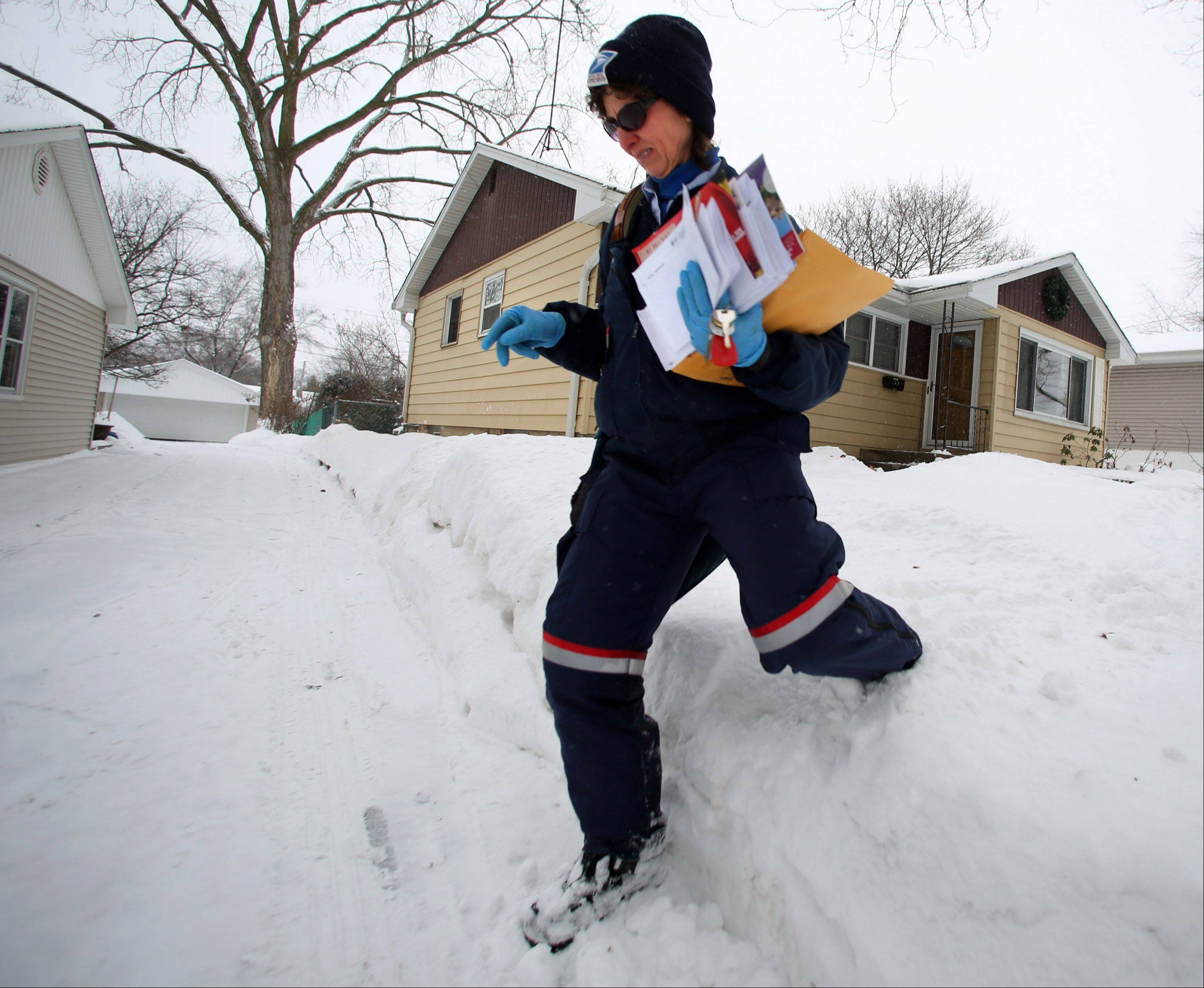 Mail carrier Bernie Szostak deliveries mail on her route on the west side of Mundelein on Saturday.