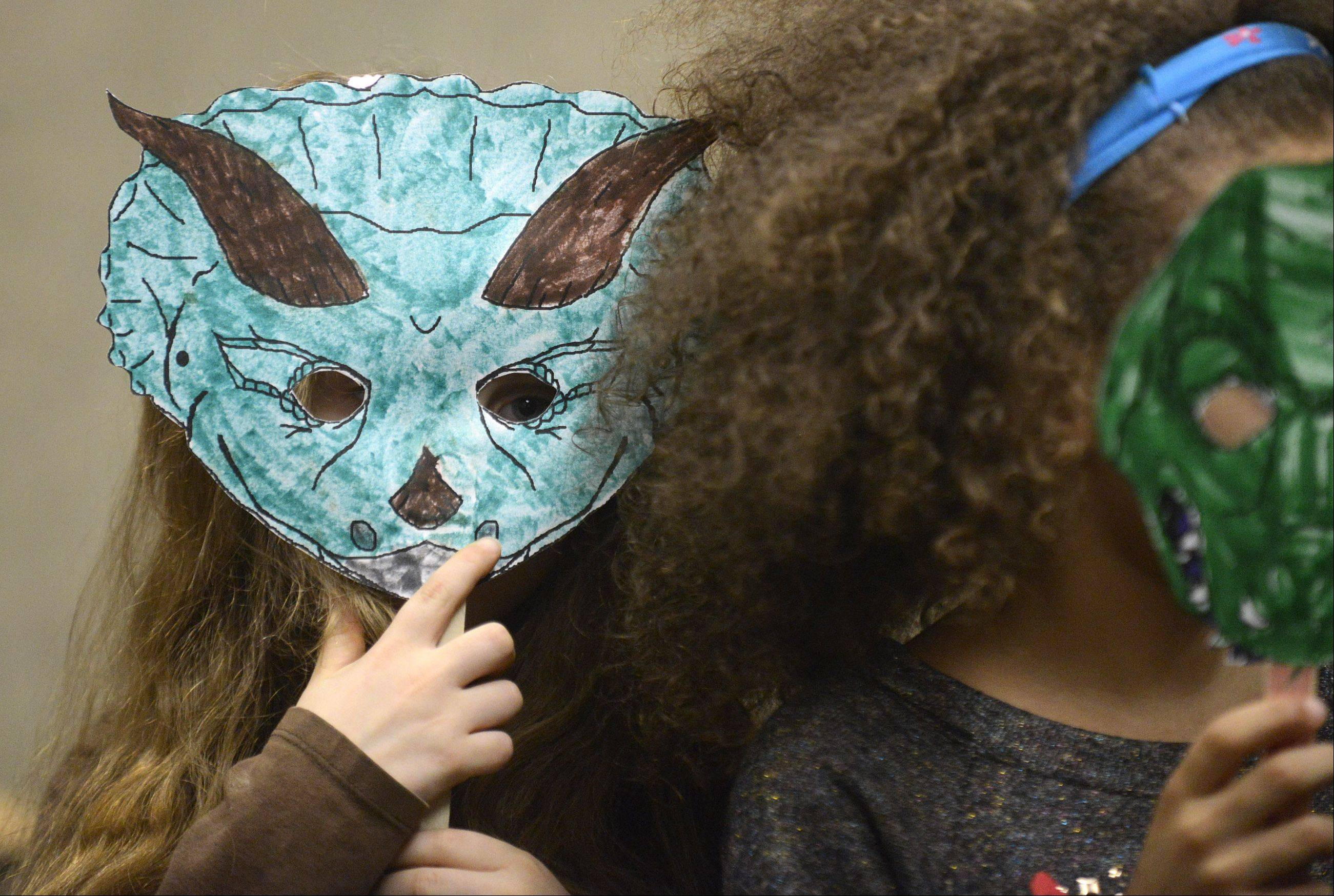 Meredith Parmele, 7, of Crystal Lake, peers out from behind her hand-colored triceratops mask as she and other children join in a dinosaur parade during a dinosaur-themed Super Saturday event for kindergarten and first graders at Algonquin Public Library. Several of the kids let loose and roared and stomped like the ancient creatures during the parade after they learned all about dinos in the Triassic, Jurassic and Cretaceous periods.