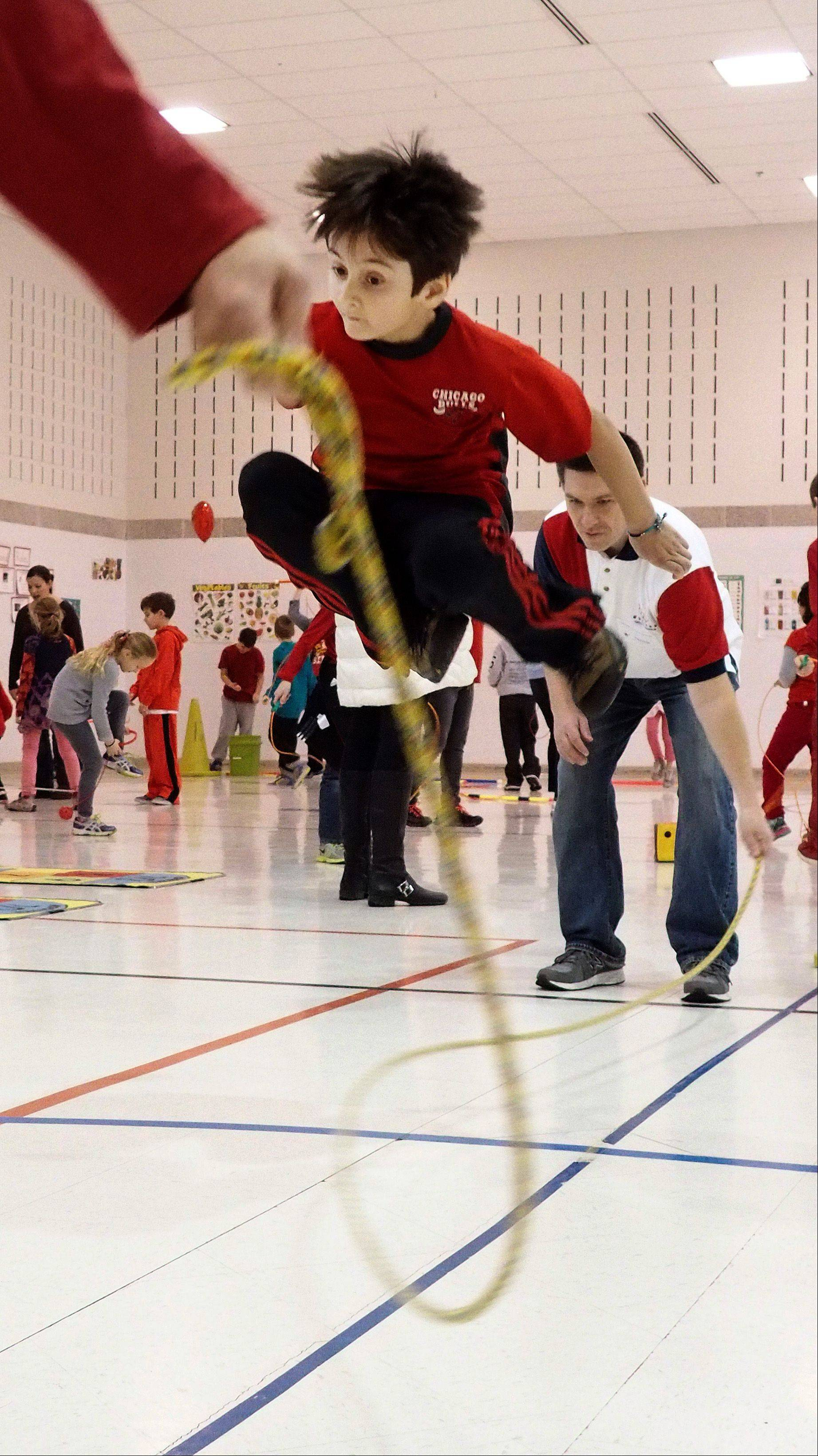 Alejandro Galbraith jumps as high as possible Friday during Longfellow School's Jump Rope for Heart program in Wheaton.