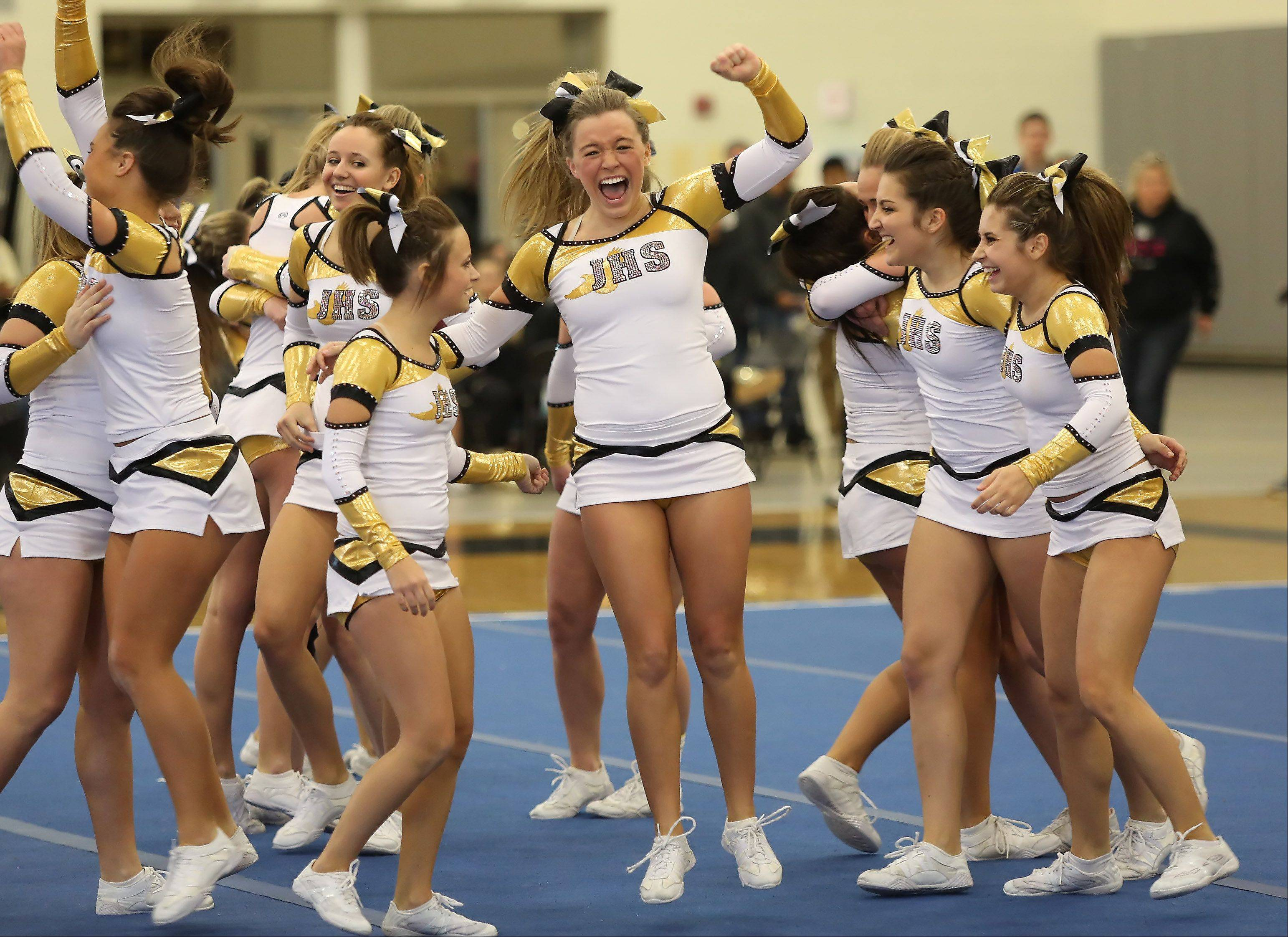 Jacobs High School cheerleader Ally Jefferson, center, jumps for joy with her teammates after they competed in the Large Team category Sunday during the IHSA Cheerleading Sectional at Grayslake North High School.