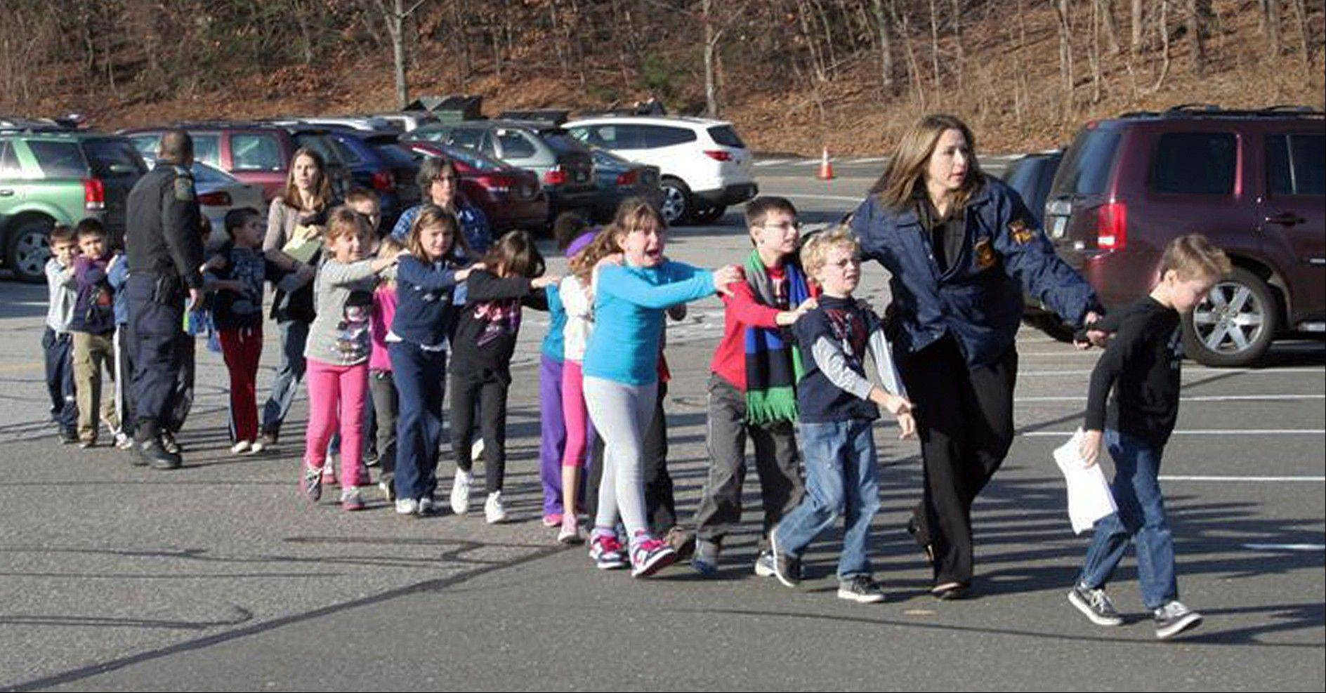 In this photo provided by the Newtown Bee, Connecticut State Police lead children from the Sandy Hook Elementary School in Newtown, Conn., following the shooting there Dec. 14, 2012.