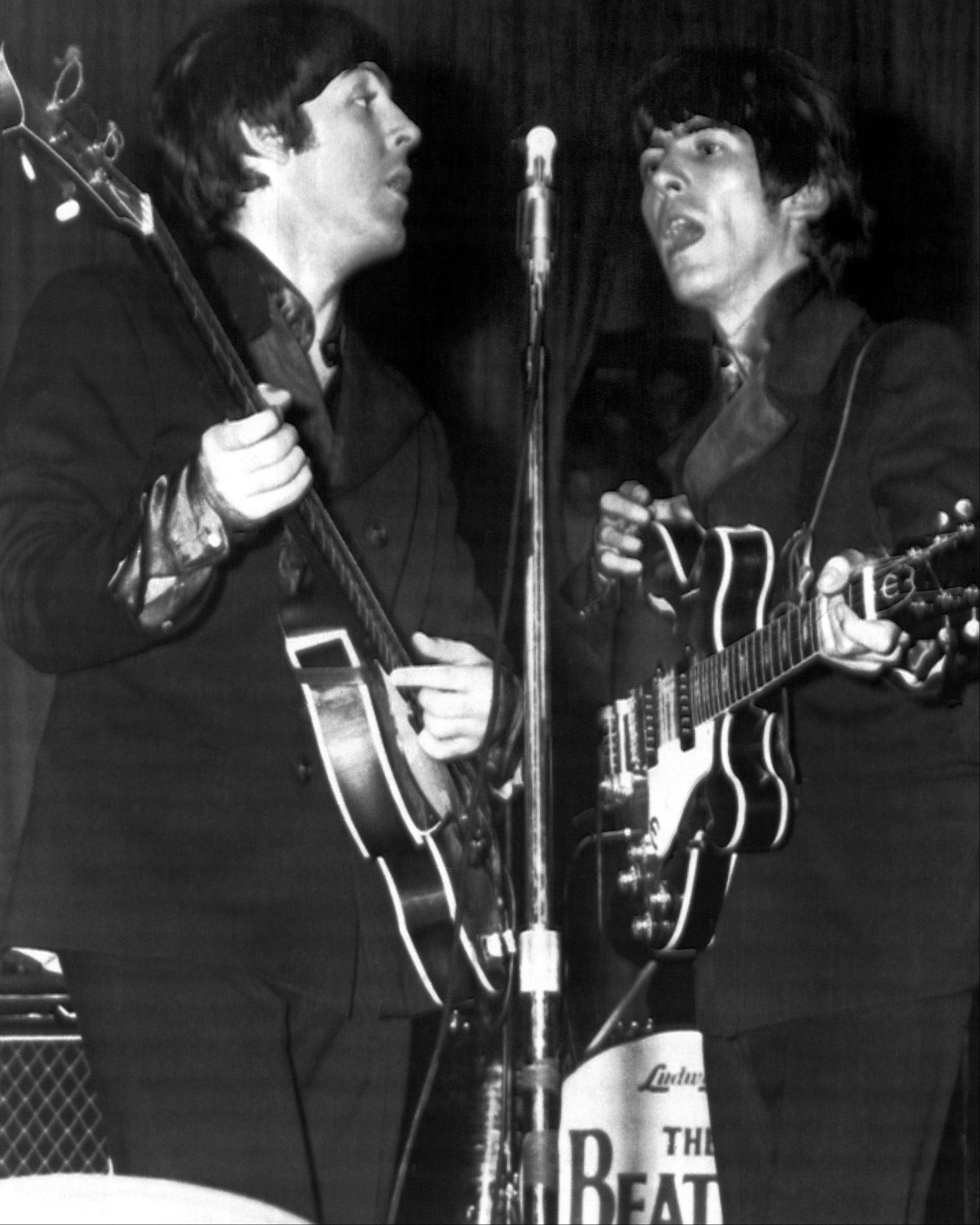 Paul McCartney, left, and George Harrison perform with The Beatles during a 1966 concert at Chicago's International Amphitheatre.