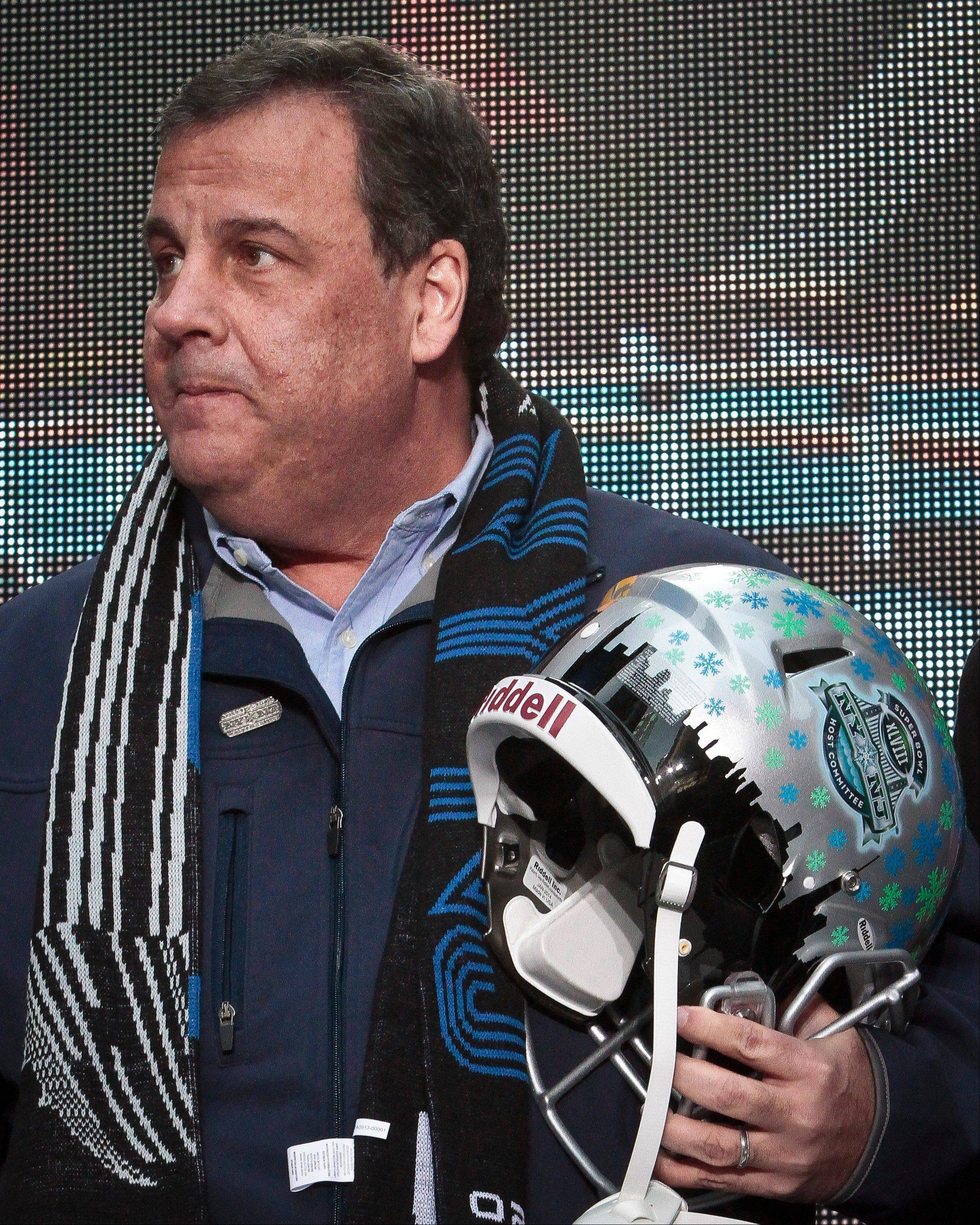 New Jersey Gov. Chris Christie holds a souvenir football helmet Saturday as he leaves after a ceremony to pass official hosting duties of next year's Super Bowl to representatives from Arizona.