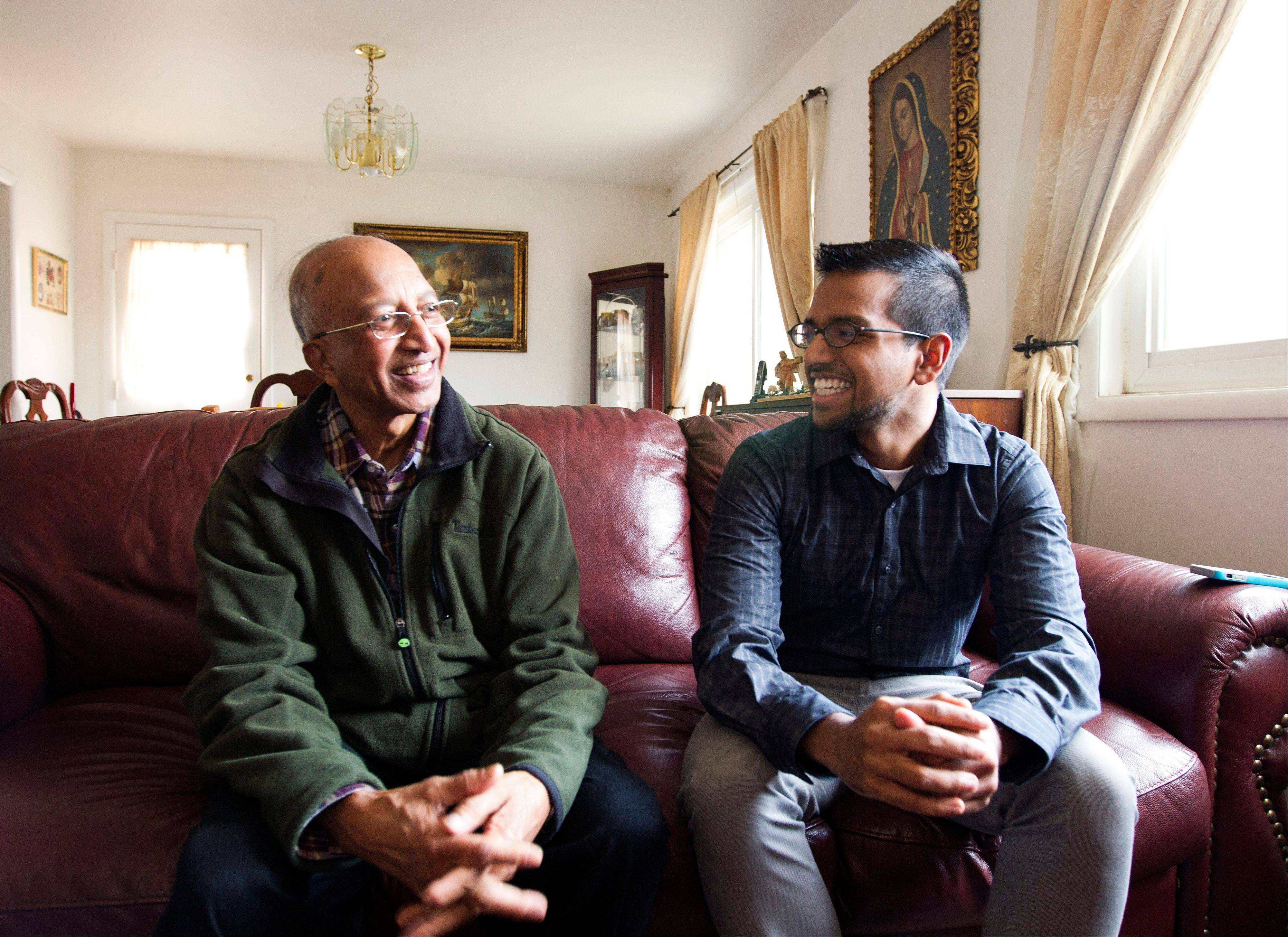 Yves Gomes, a student at the University of Maryland, who's parents were deported, right, talks Friday to his great uncle Henry Gomes, in his great uncle's house where he lives, in Silver Spring, Md.,
