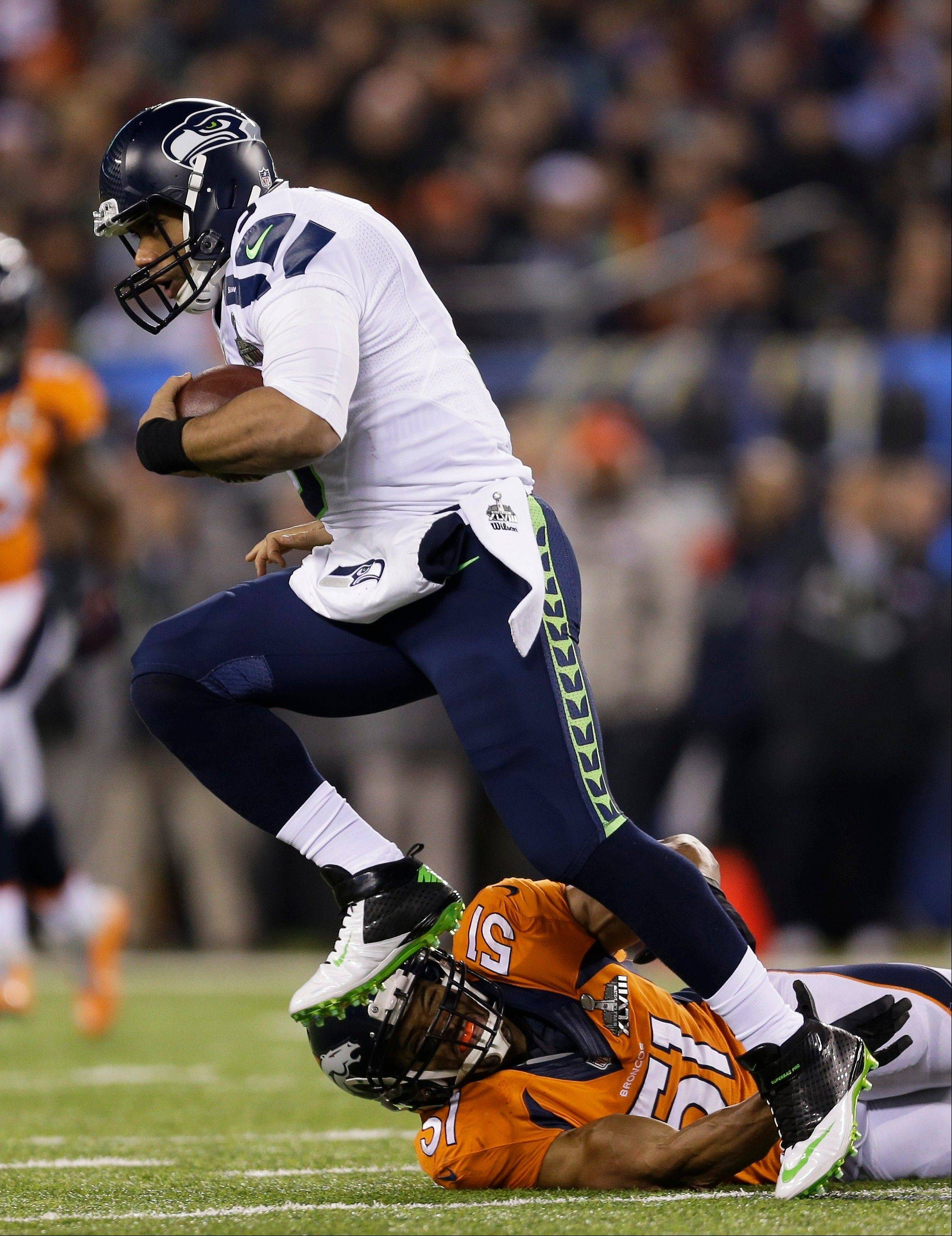 Seahawks quarterback Russell Wilson runs from Broncos defender Paris Lenon during the second half Sunday night.