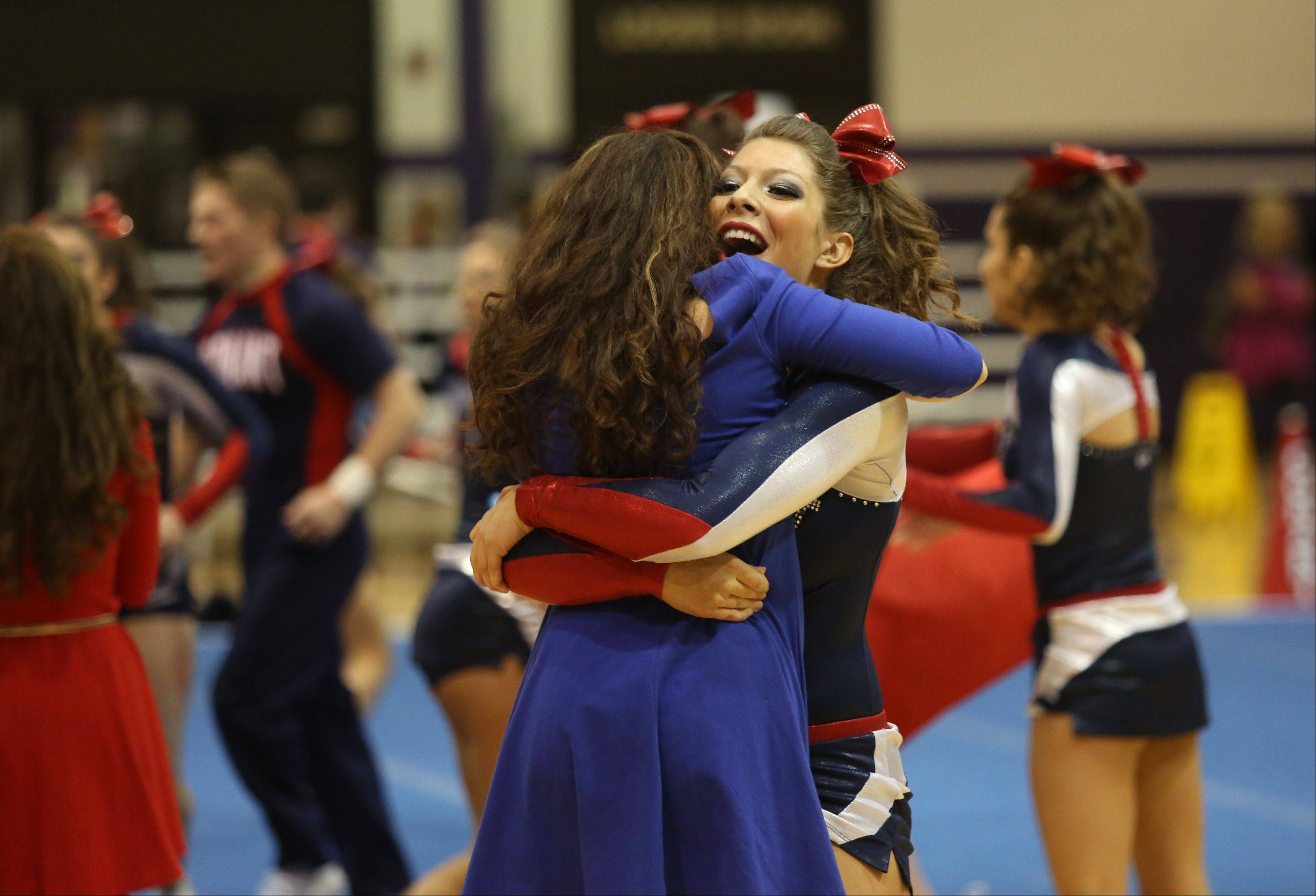 Conant High School cheerleader Lauren Cullen hugs her coach after competing in the Coed Team category during the IHSA Cheerleading Sectional Sunday hosted by Rolling Meadows High School.