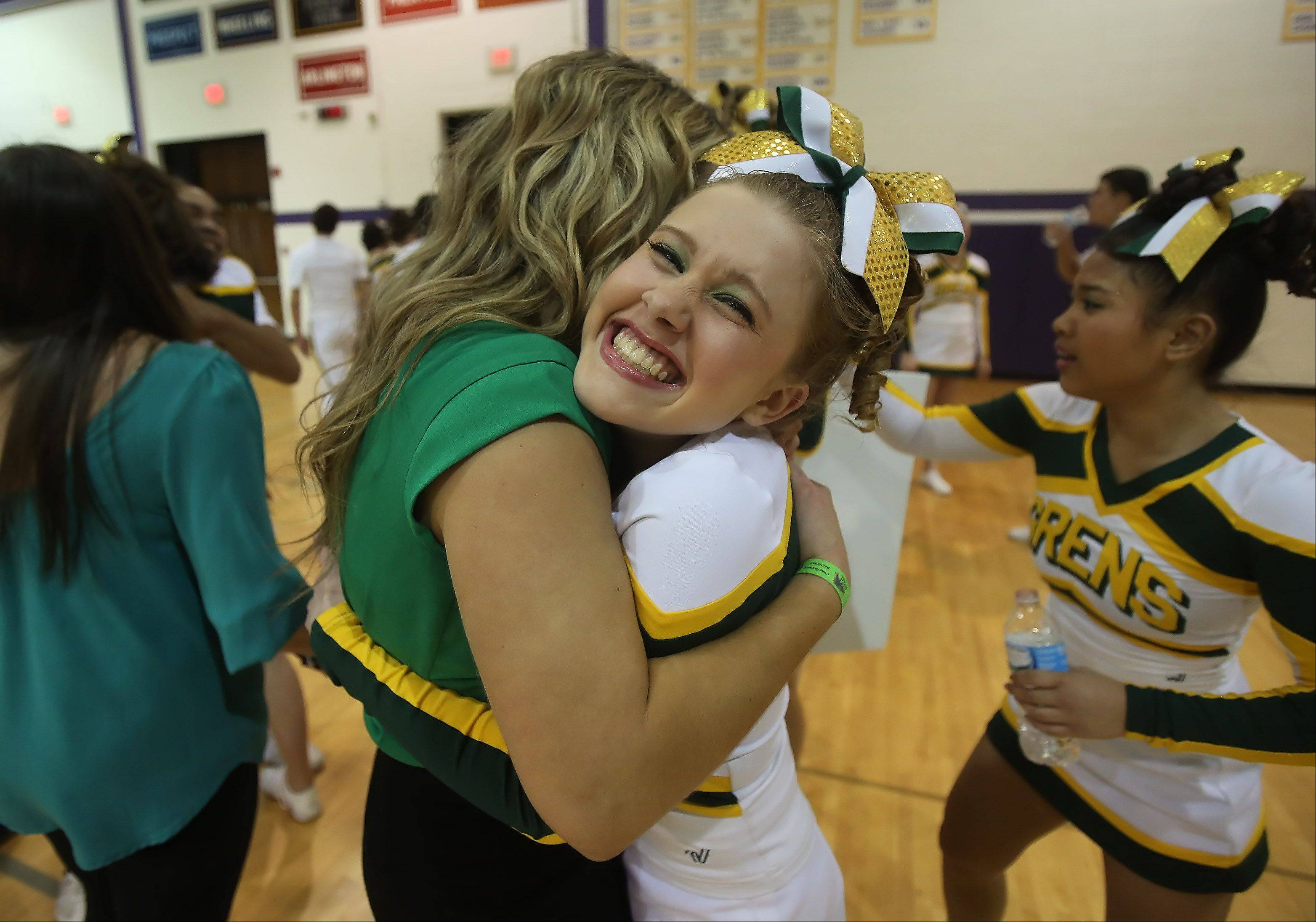 Elk Grove High School cheerleader Danielle Haffey hugs her coach Danielle Damato after the team competed in the Coed Team category during the IHSA Cheerleading Sectional Sunday hosted by Rolling Meadows High School.
