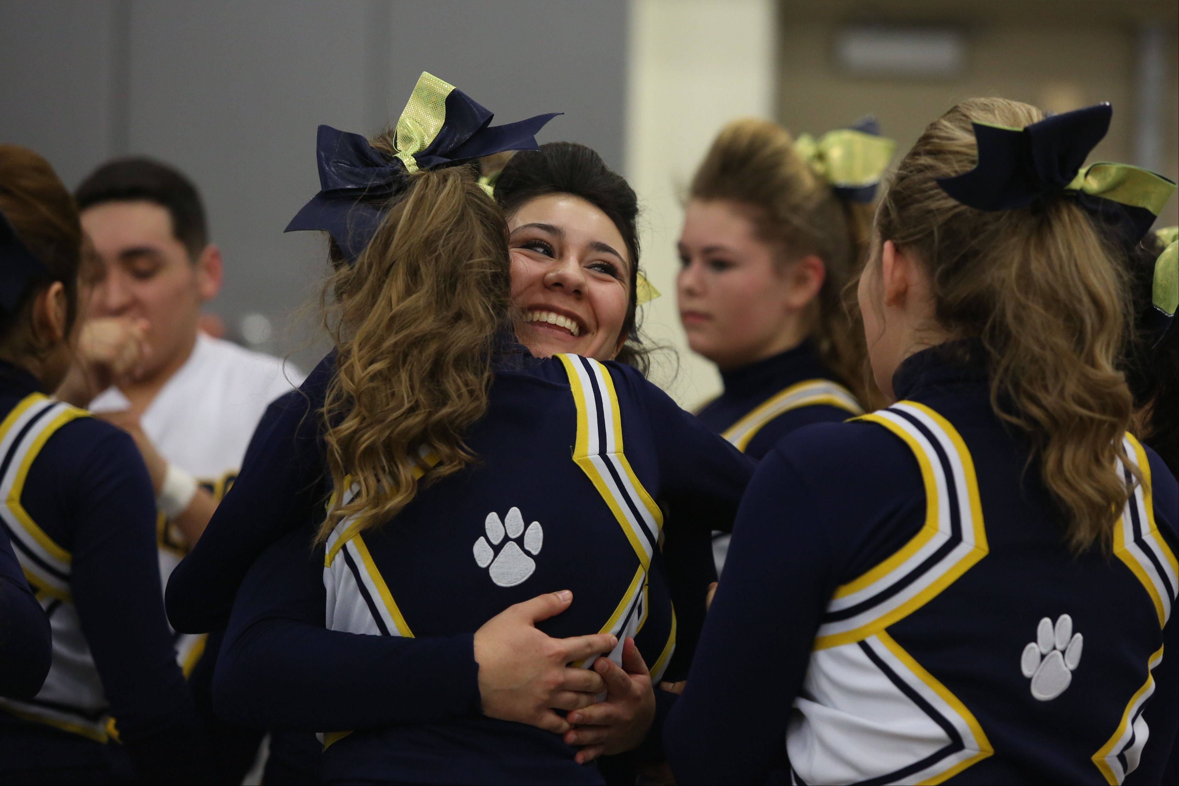 Round Lake High School cheerleaders hug after competing in the Large Team category during the IHSA Cheerleading Sectional Sunday hosted by Grayslake North High School.