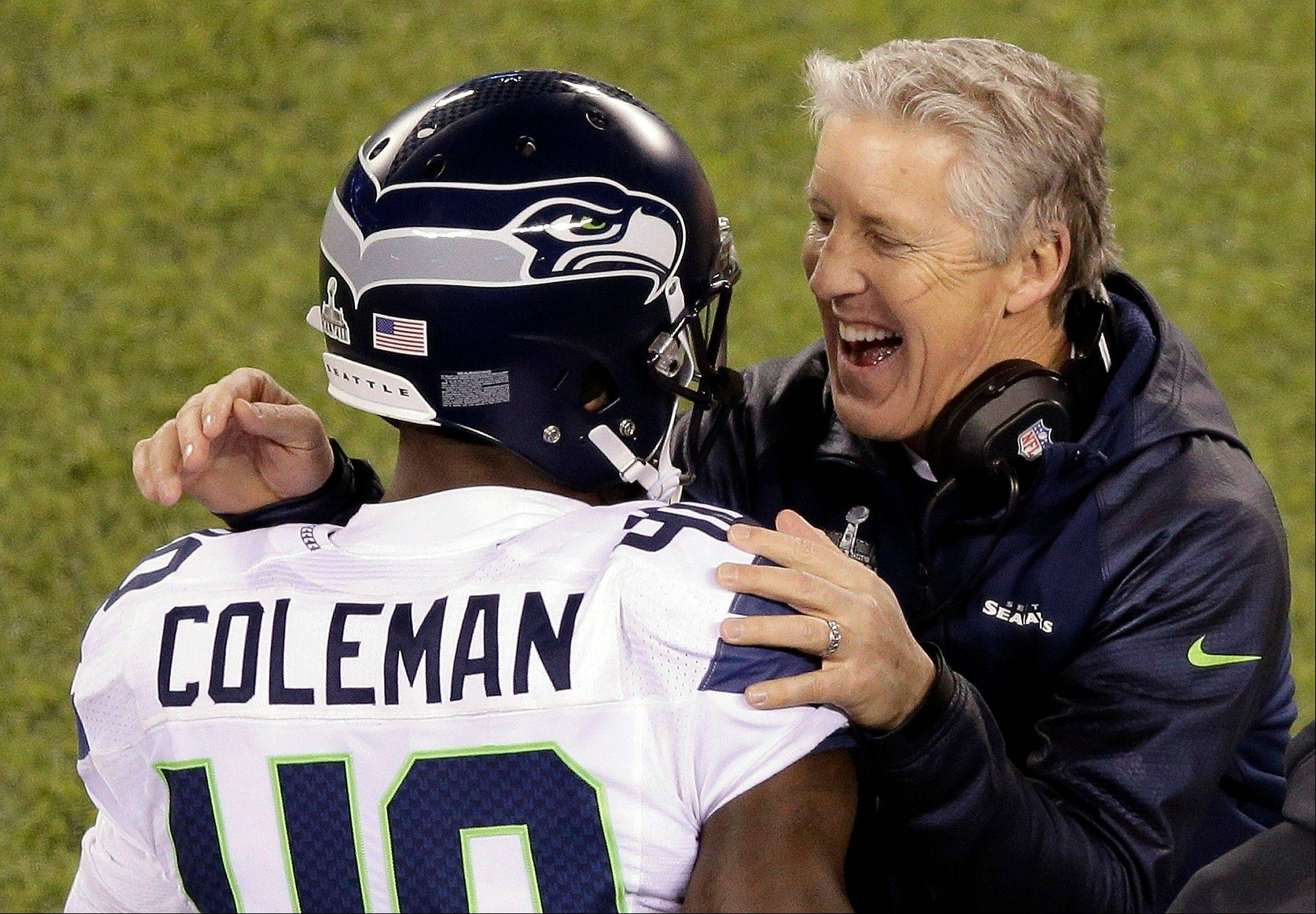 Seattle Seahawks head coach Pete Carroll laughs with Derrick Coleman (40) during the second half of the NFL Super Bowl XLVIII football game against the Denver Broncos Sunday, Feb. 2, 2014, in East Rutherford, N.J.