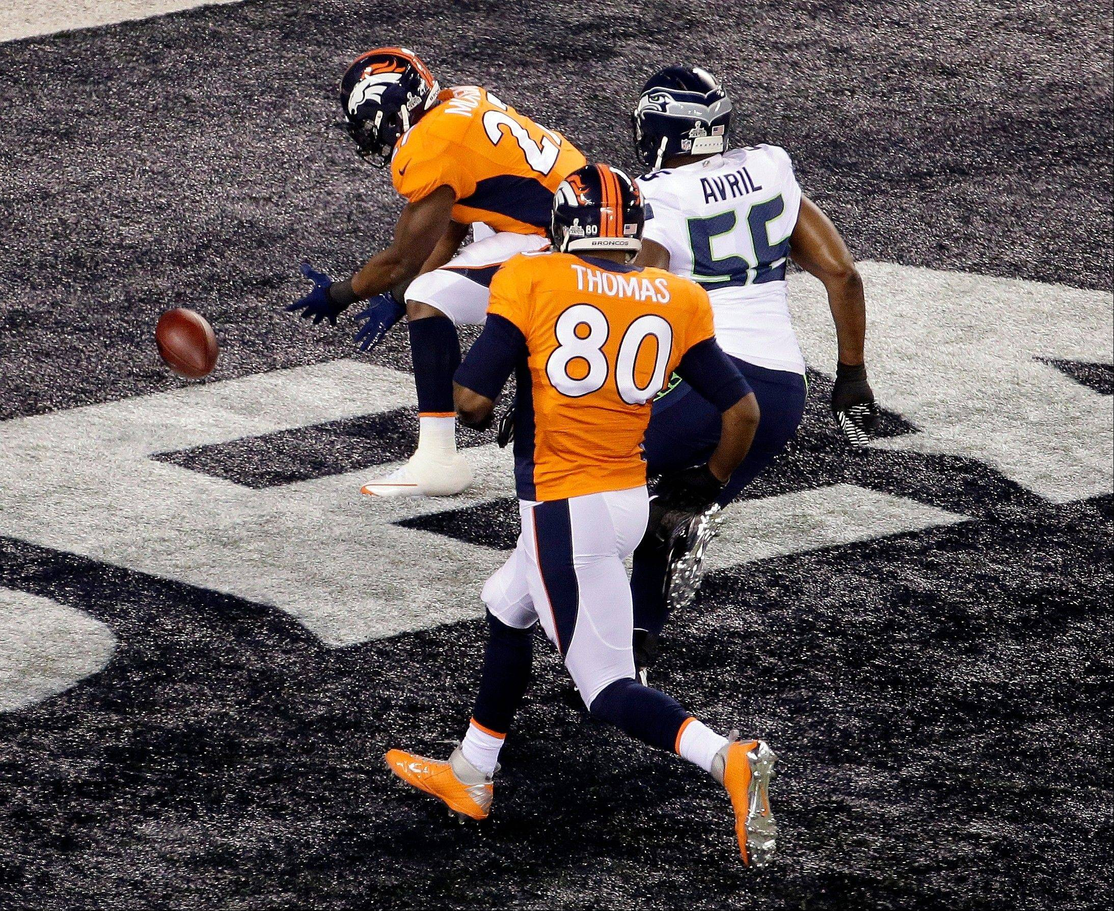 Denver Broncos' Knowshon Moreno (27) recovers the football in the end zone for a safety as Seattle Seahawks' Heath Farwell (55) and teammate Julius Thomas (80) chase him during the first half of the NFL Super Bowl XLVIII football game Sunday, Feb. 2, 2014, in East Rutherford, N.J.