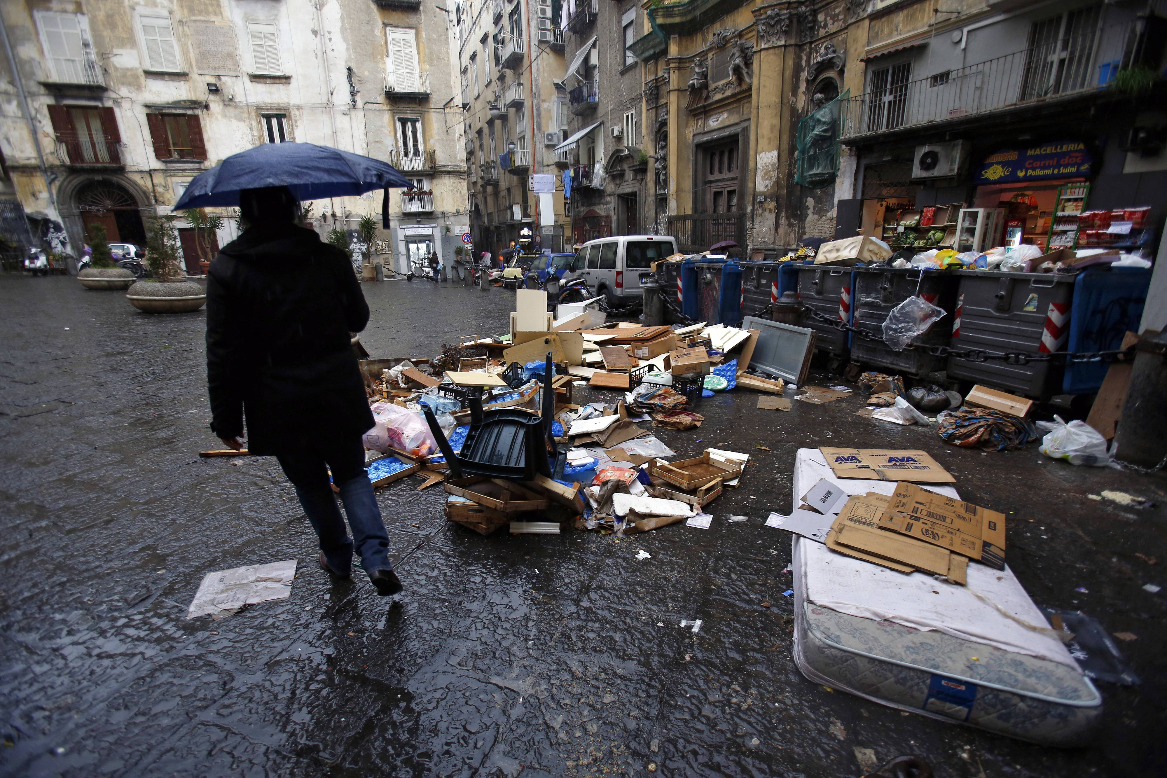 A pedestrian passes a pile of garbage strewed around trash cans outside a store in Naples, Italy, on Saturday, Feb. 1, 2014. In Naples, the local youth unemployment rate in 2012 was 53.6 percent compared to a national average of 35.3 percent. Photographer: Alessia Pierdomenico/BloombergBloomberg News