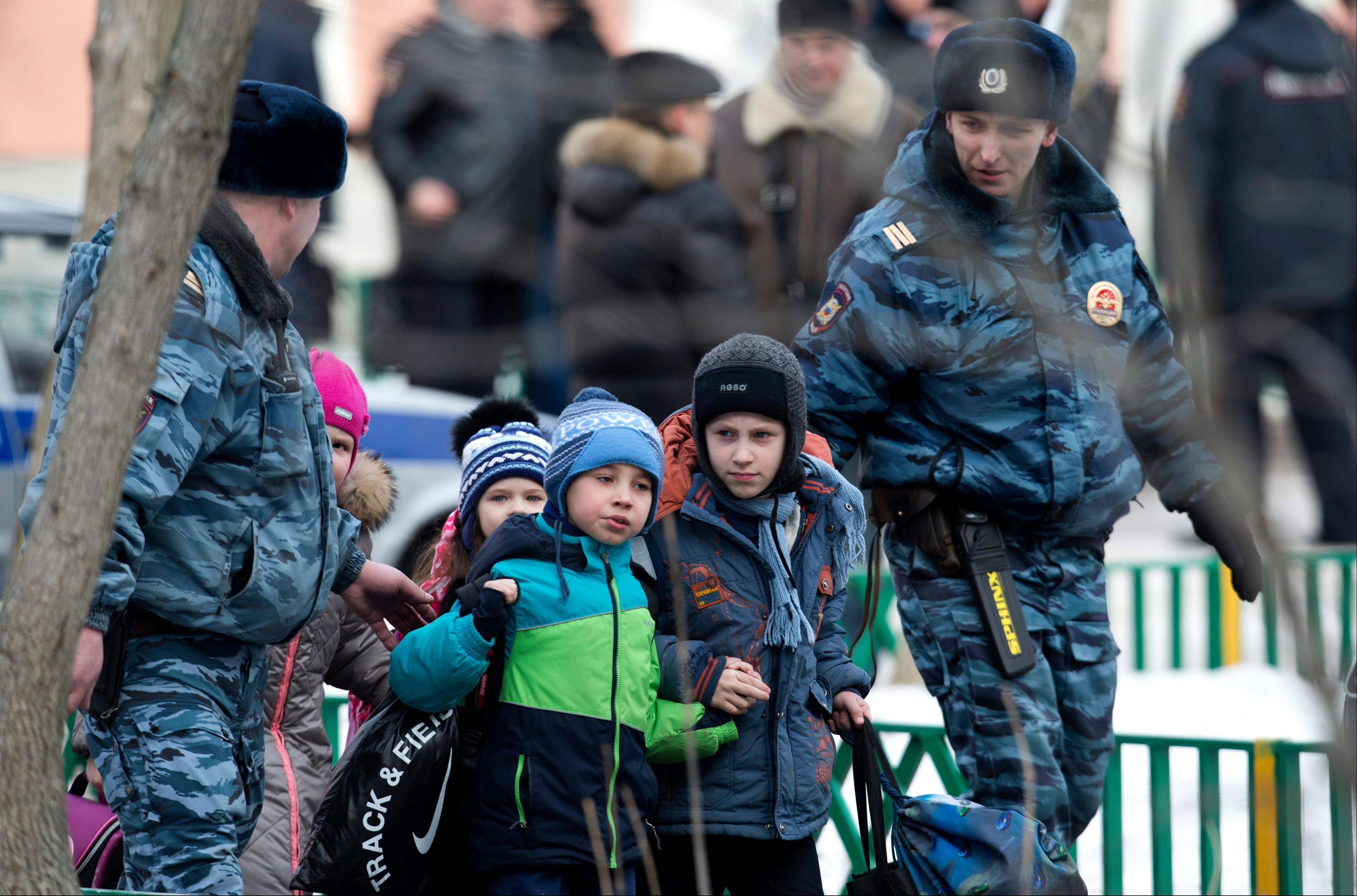 Police officers evacuate children from a Moscow school on Monday, Feb. 3, 2014. An armed teenager burst into his Moscow school on Monday and killed a teacher and policeman before being taken into custody, investigators said.
