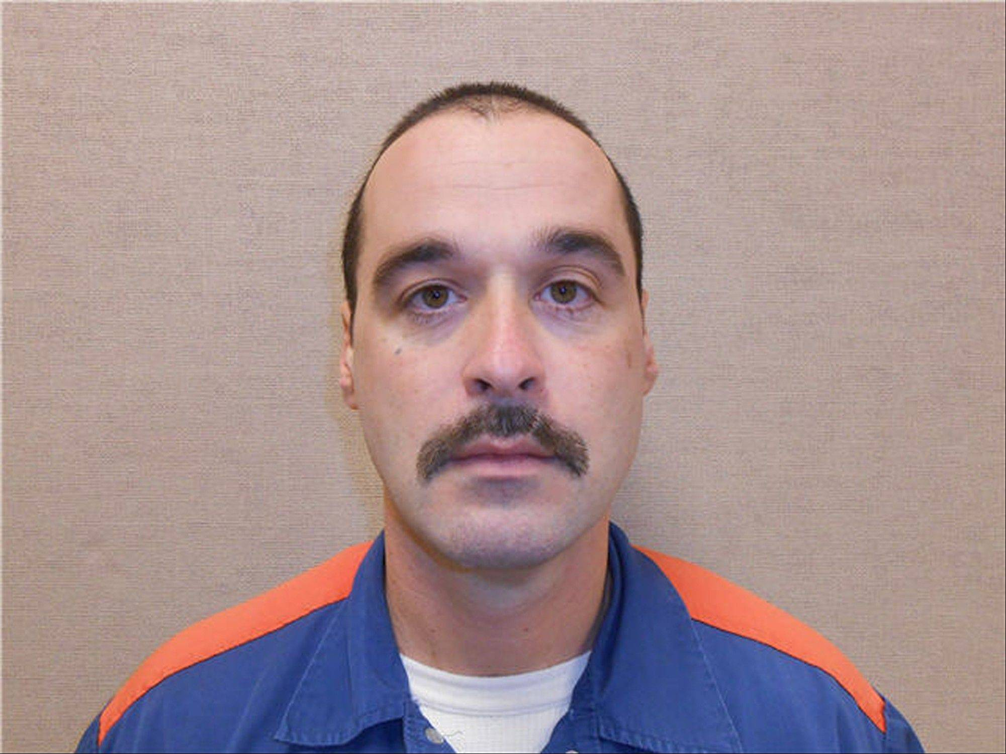 Michael David Elliot, 40, who is serving life behind bars for murder in four 1993 deaths in Michigan, is at large after he escaped from a Michigan prison and abducted a woman who fled his grips when he stopped for gas in Indiana, authorities said Monday.