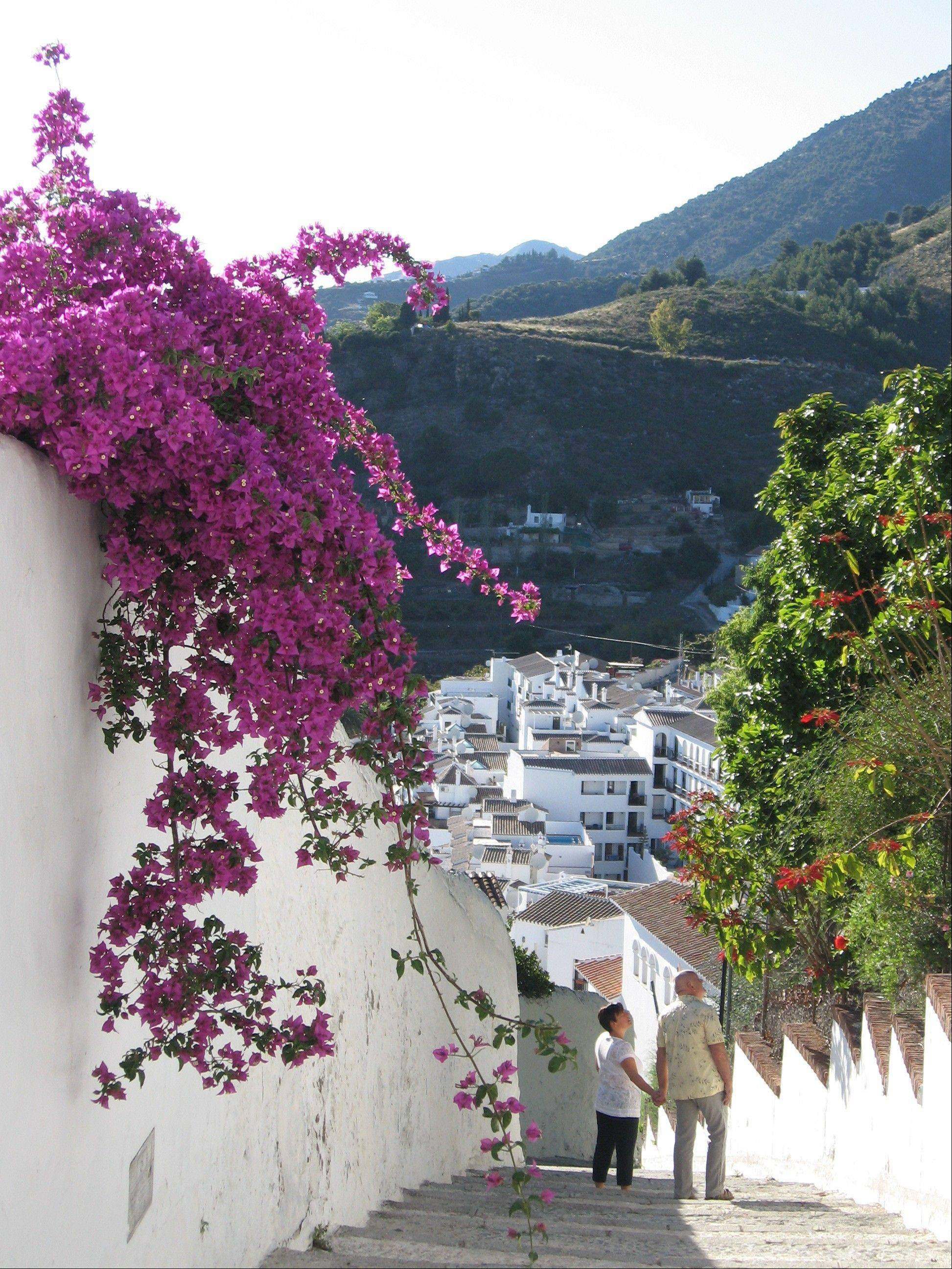 "Pink bougainvillea flowers decorate the narrow alleys of Frigiliana. One of Spain's ""pueblos blancos,"" or white villages, the ancient town sits high above the Mediterranean coast."
