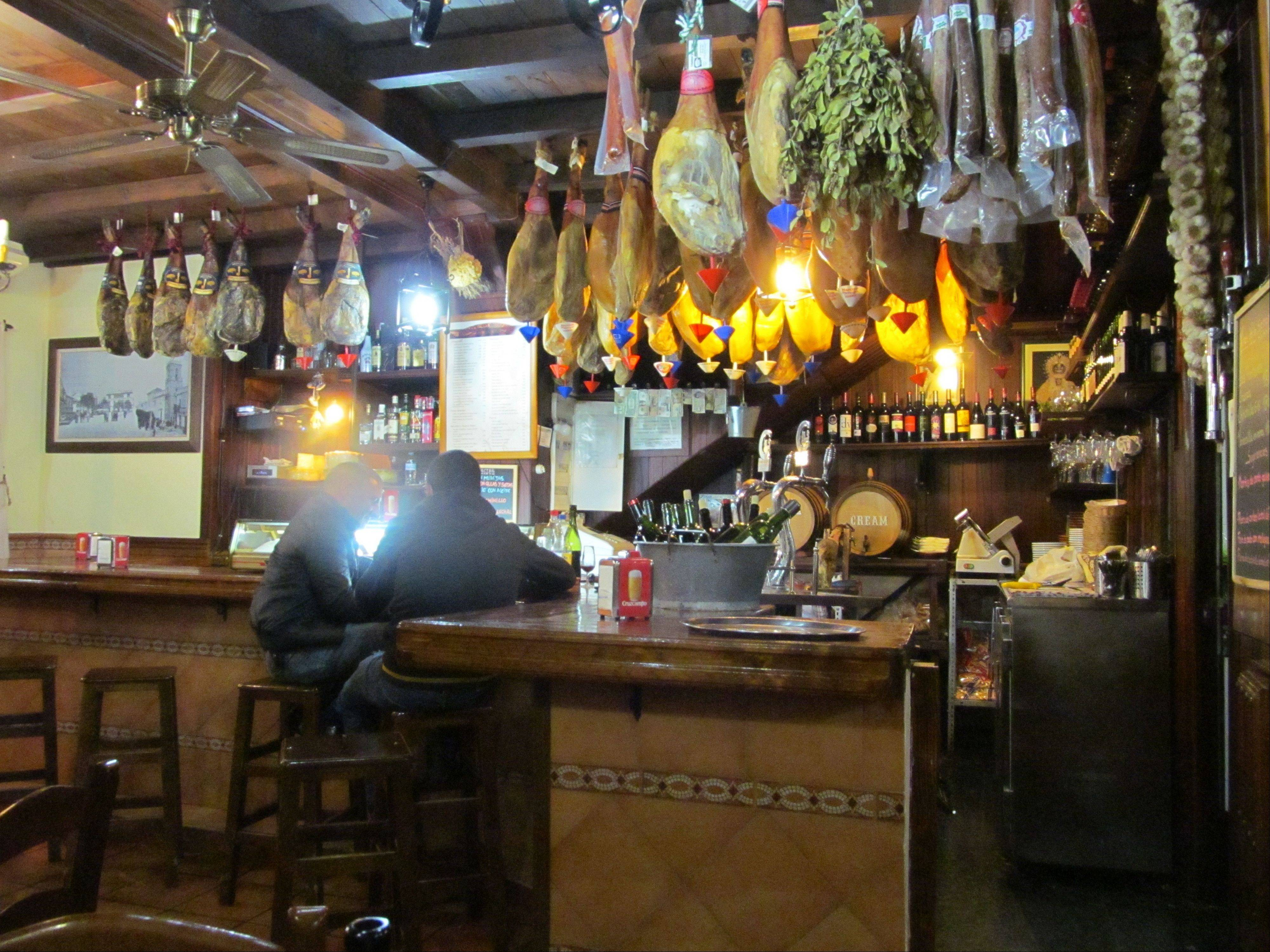 "Spain's prized hams hang over the bar at Bodega el Socorro in Ronda, one of the most monumental of ""pueblos blancos,"" or white villages, in the southern region of Andalusia."