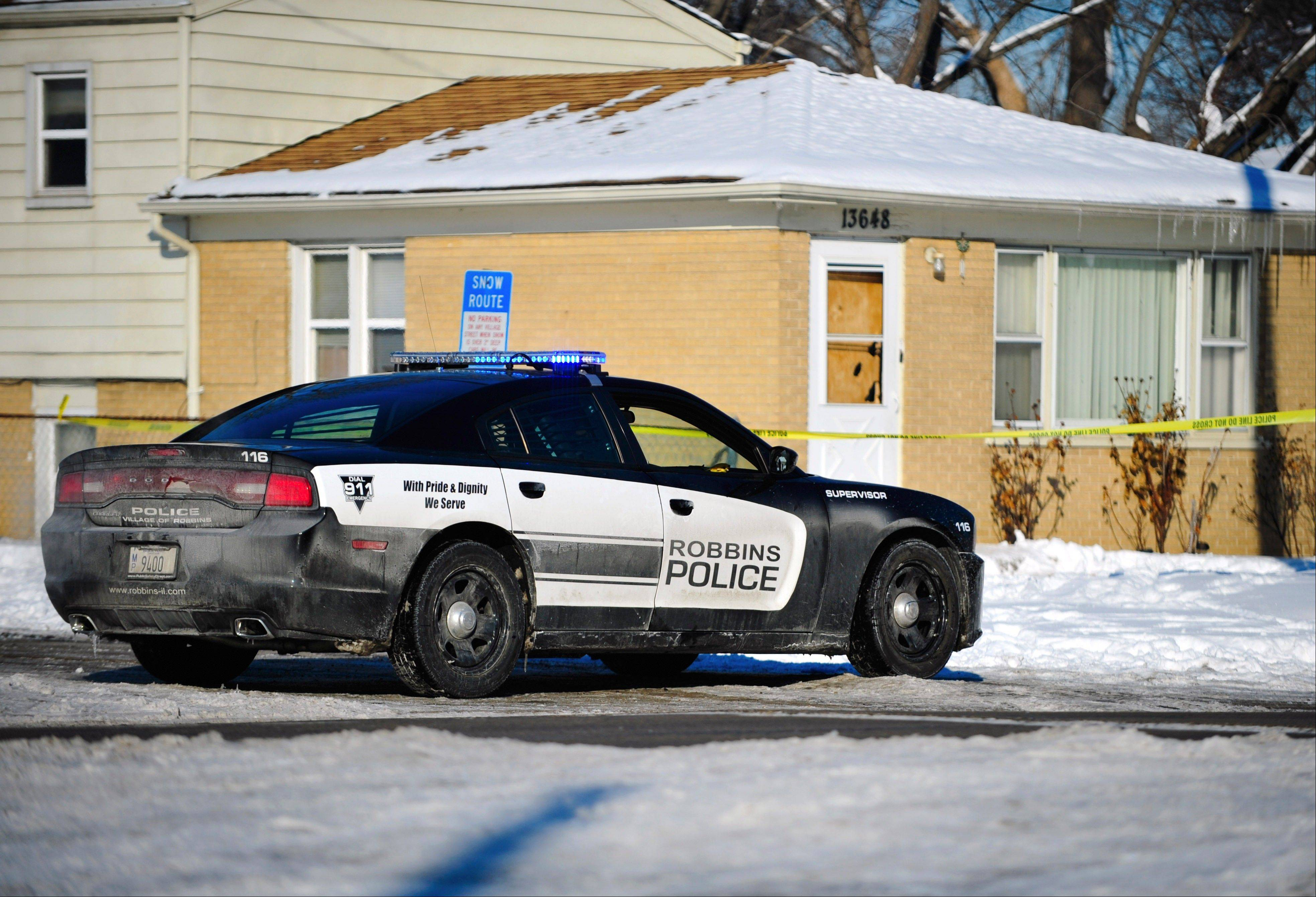 A Robbins police car is seen parked outside a home Monday where, police say, 43-year-old Michael Worsham shot and killed his wife and two of his children Sunday before he died of unknown causes.