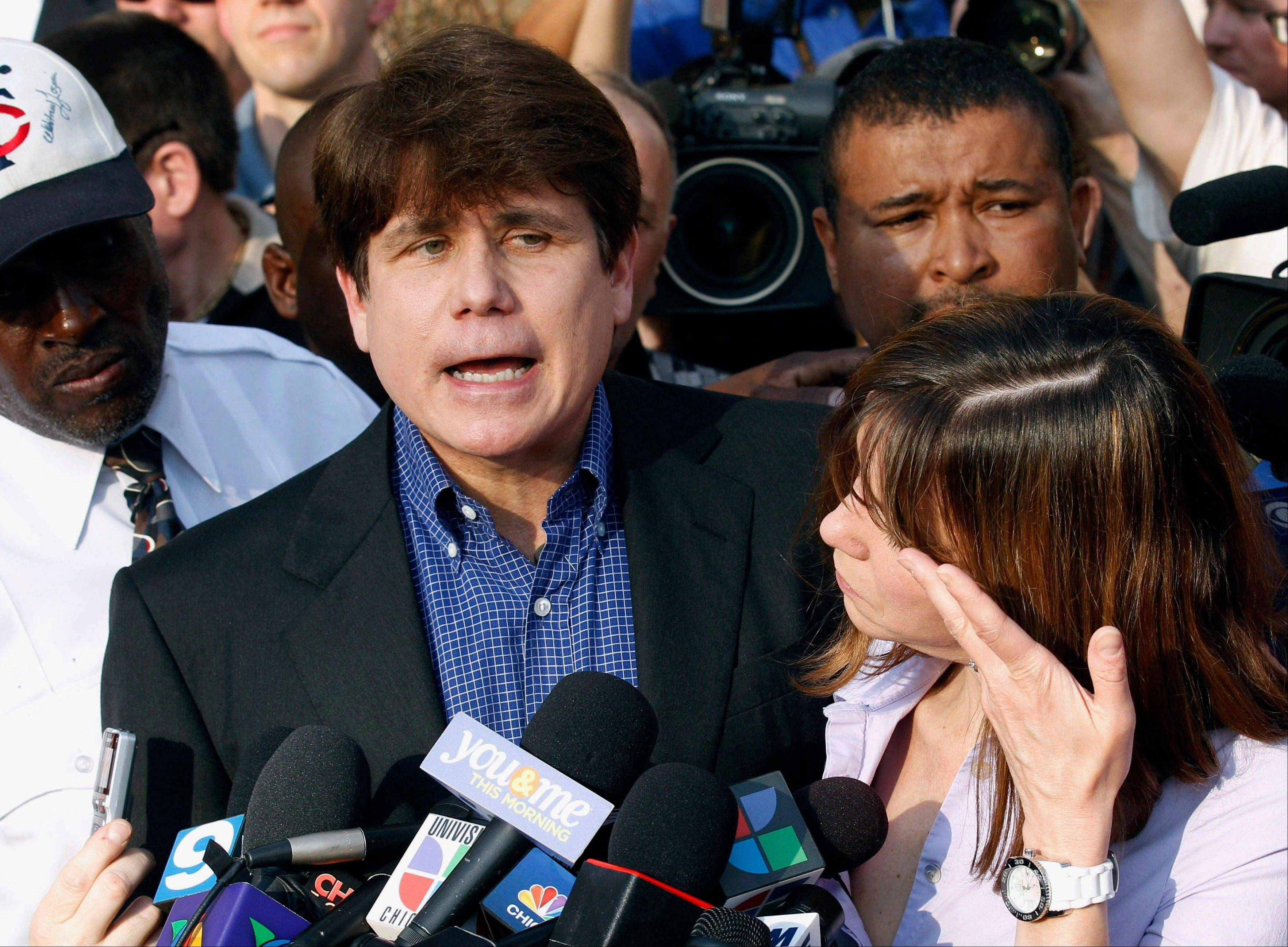 Former Gov. Rod Blagojevich speaks to the media outside his home in Chicago, as his wife, Patti, wipes away tears a day before he was to report to prison in Littleton, Colo.