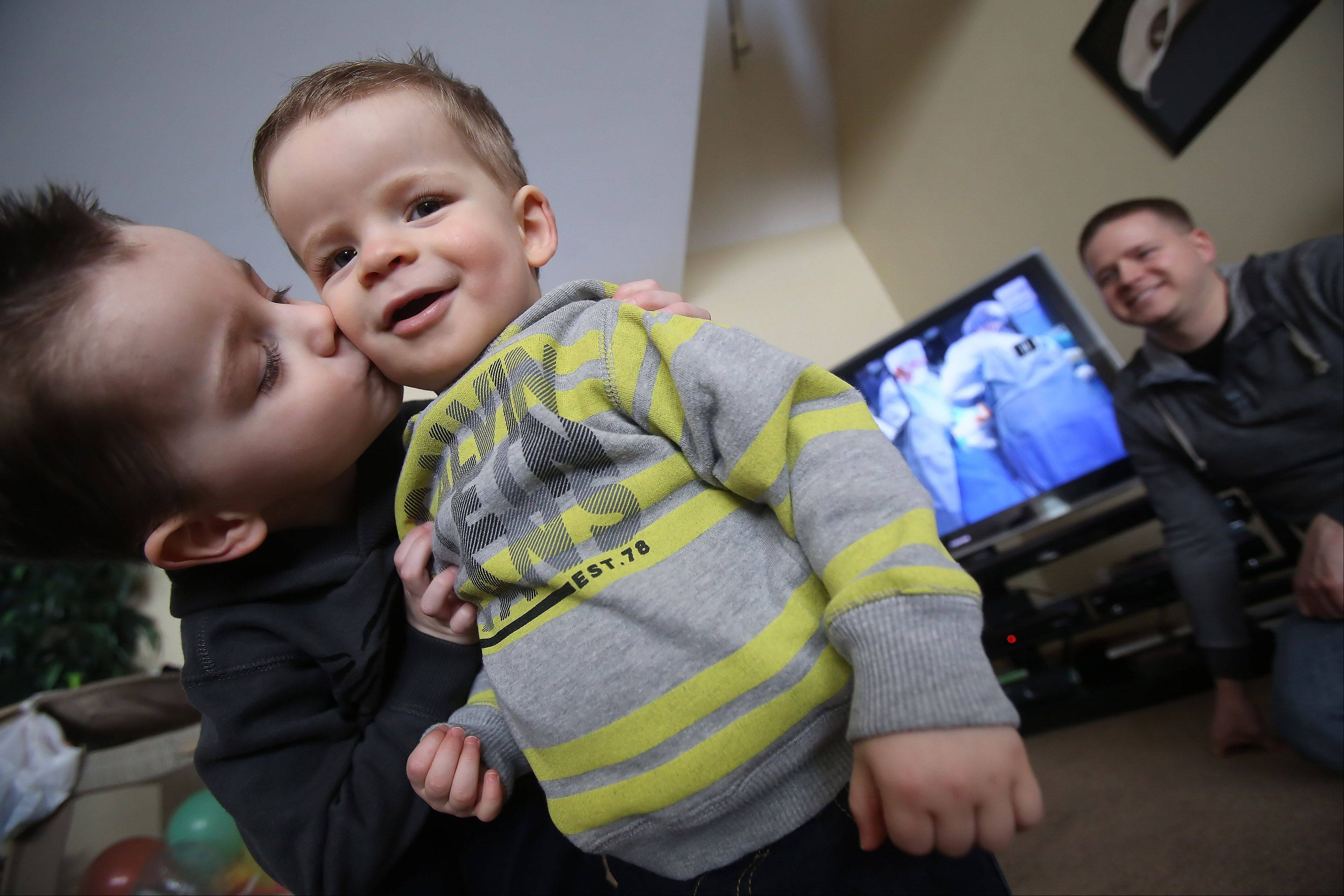 Dean Bacon, 3, kisses his 18-month-old brother Christopher as his father, Greg, watches. Dean's 2010 birth was featured on national TV Sunday as part of Microsoft's Super Bowl ad.
