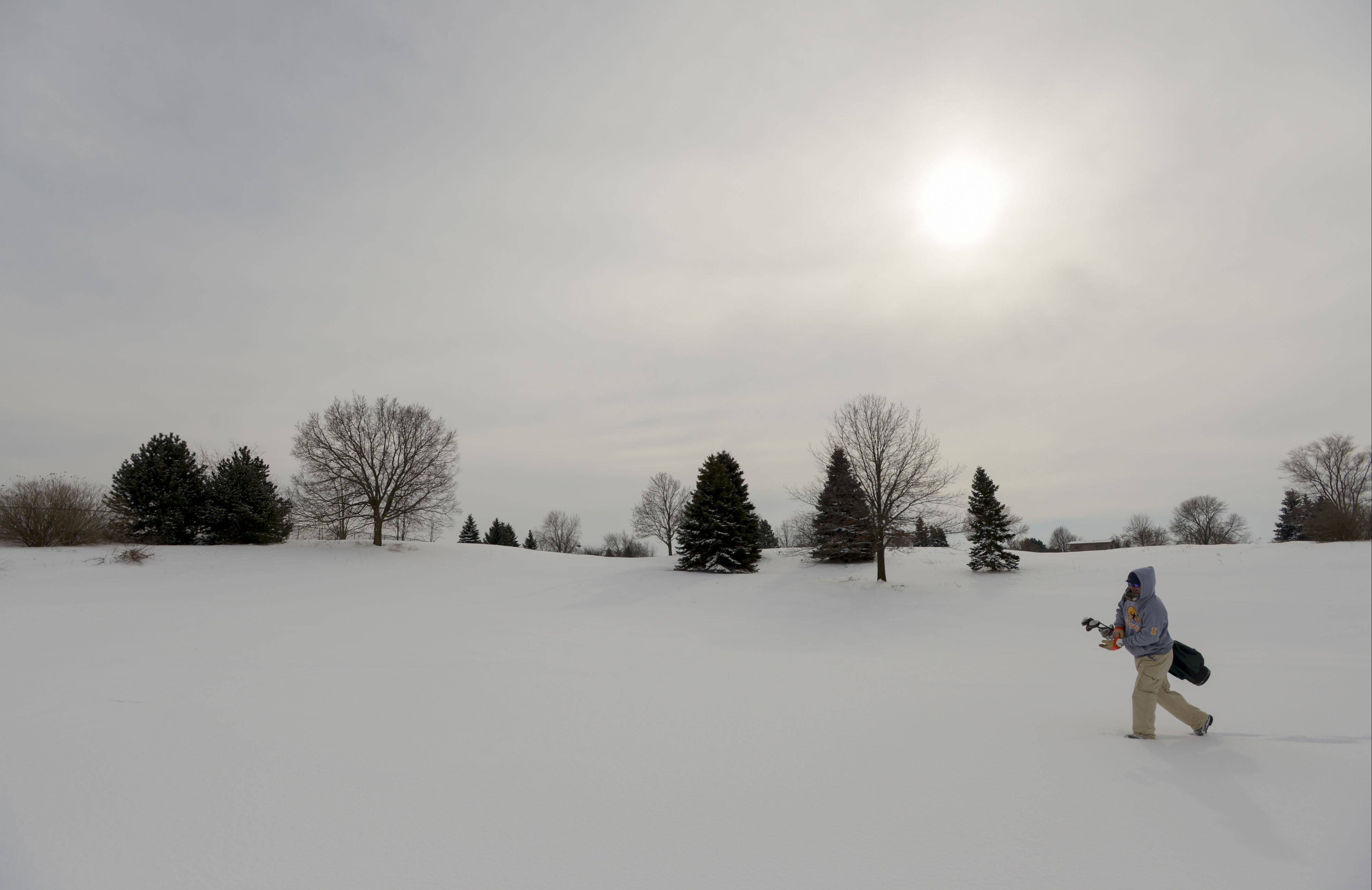 Jordan Troutman of Aurora treks through the snow toward the 10th green Sunday at Springbrook Golf Course in Naperville. Troutman was part a group maintaining a 28-year tradition of playing golf on Super Bowl Sunday regardless of the weather.